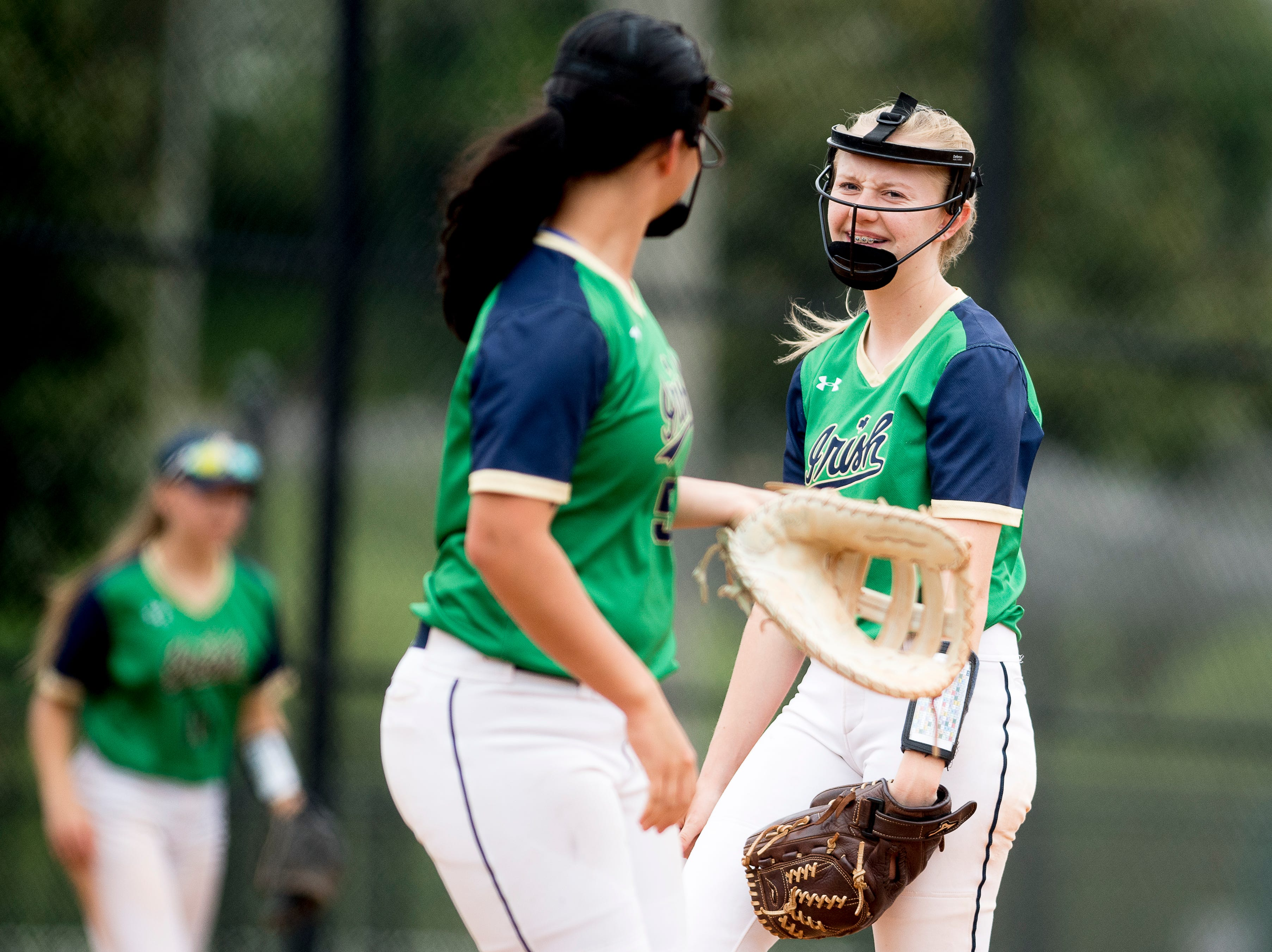Catholic's Bri Costello (8) laughs with first baseman Emma Schaad (55) during a softball game between Catholic and Karns at Caswell Park in Knoxville, Tennessee on Friday, April 12, 2019.