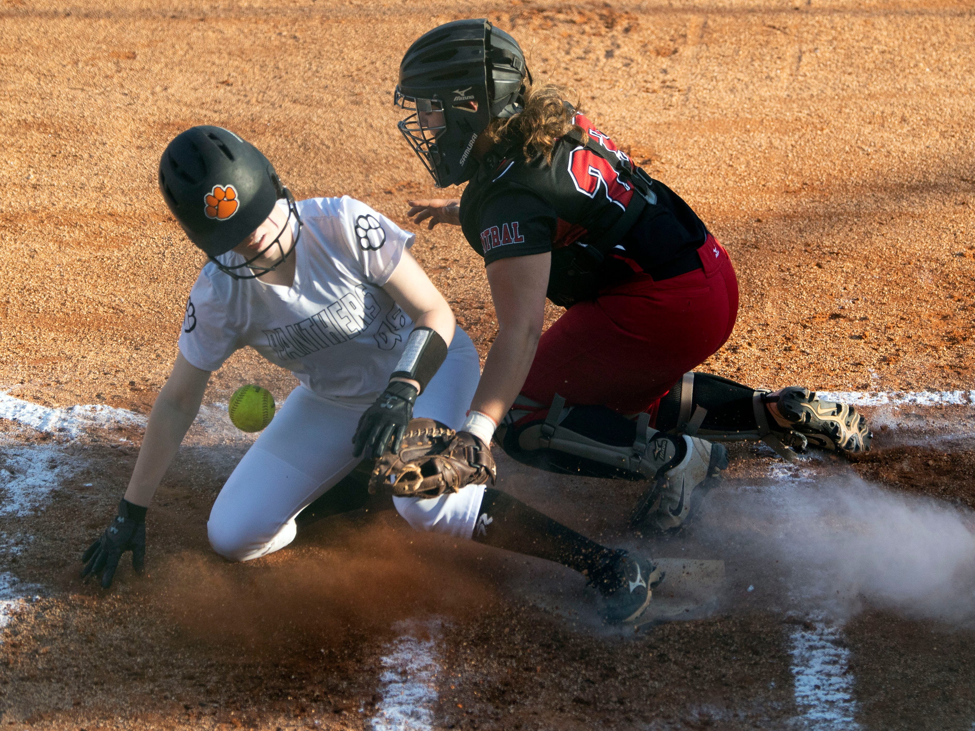 Powell's Alaina Watson (48) is ruled safe at home after Central's Savana Hurd (23) drops the ball on the tag on Thursday, April 11, 2019.