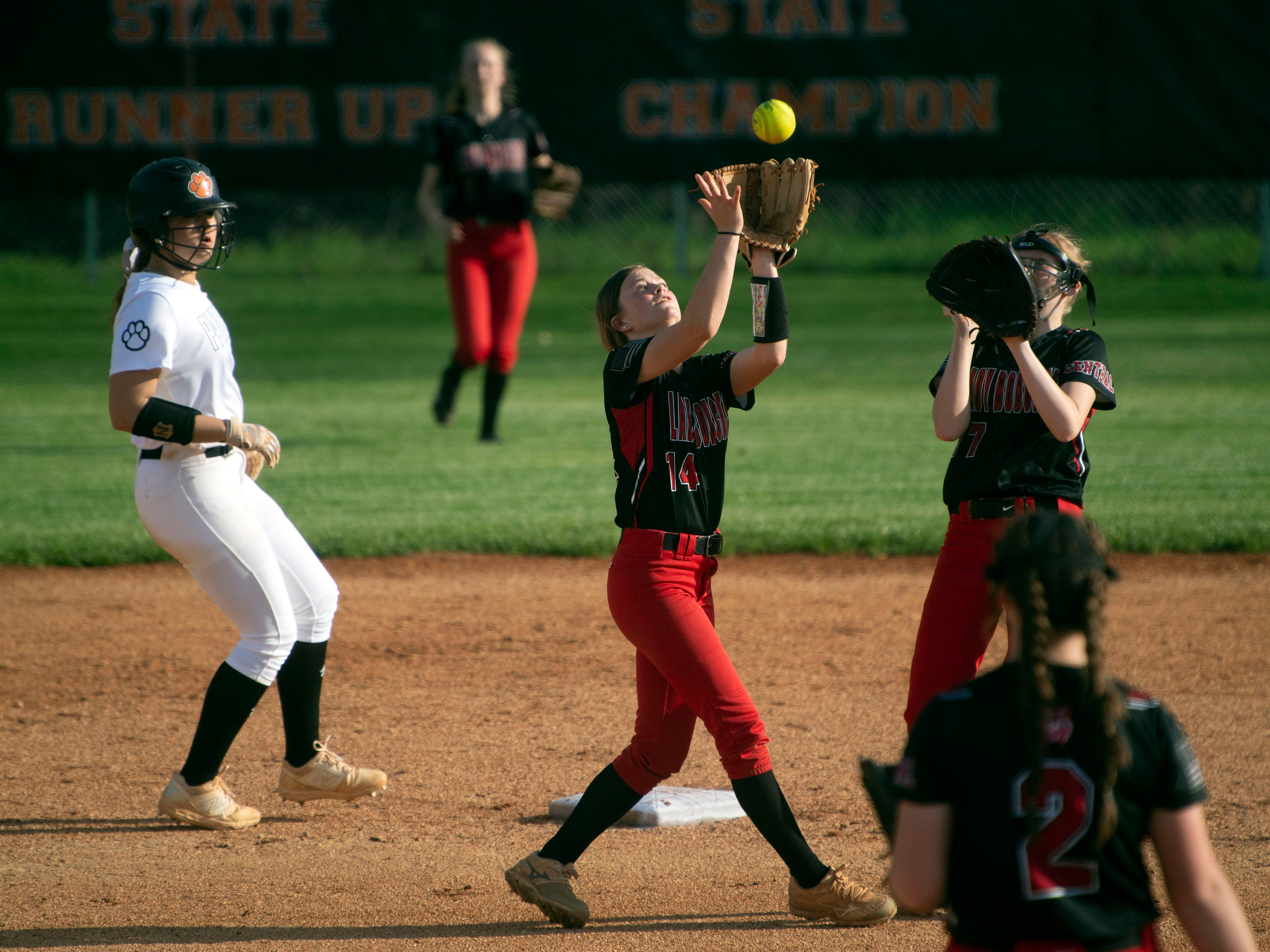 Central's Maycee Limbaugh (14) catches a fly ball in the game at Powell on Thursday, April 11, 2019.