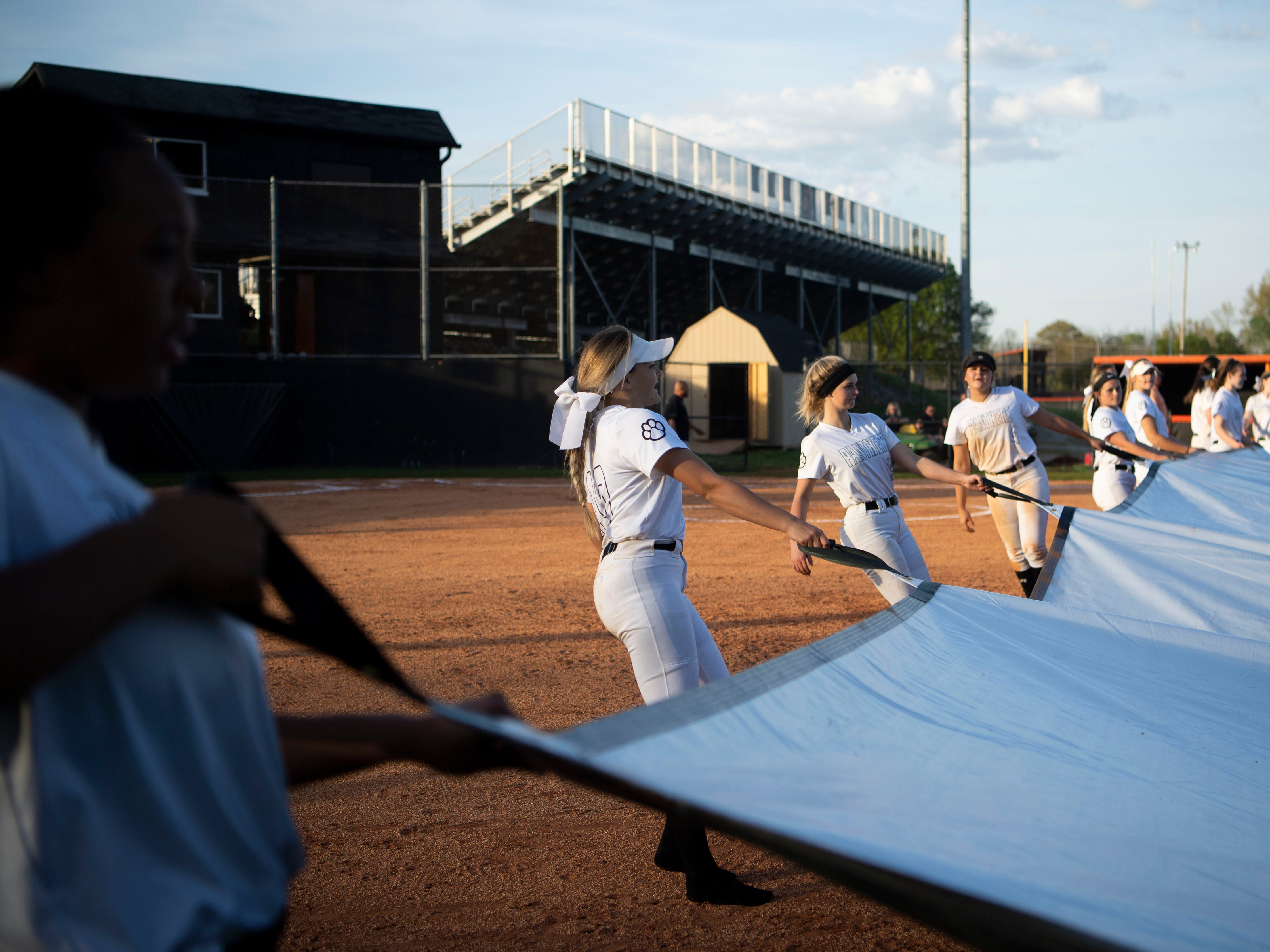Powell players work together to cover their infield after their game against Central on Thursday, April 11, 2019. It was the team's first game at home after rains destroyed the field earlier in the year.