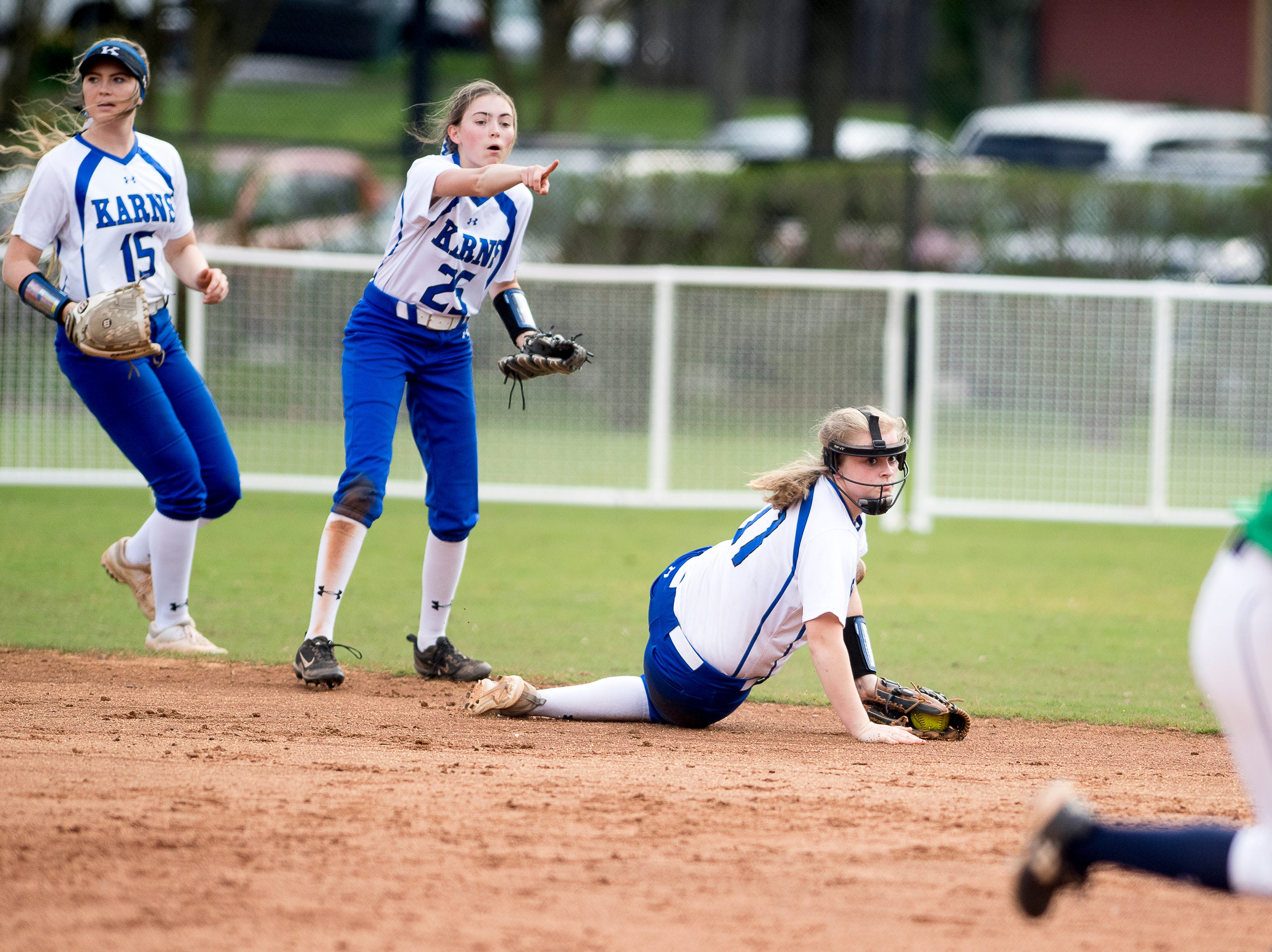 Karns' Elizabeth Breeden (25) points Kelcie Jade Grubb (17) to home plate during a softball game between Catholic and Karns at Caswell Park in Knoxville, Tennessee on Friday, April 12, 2019.