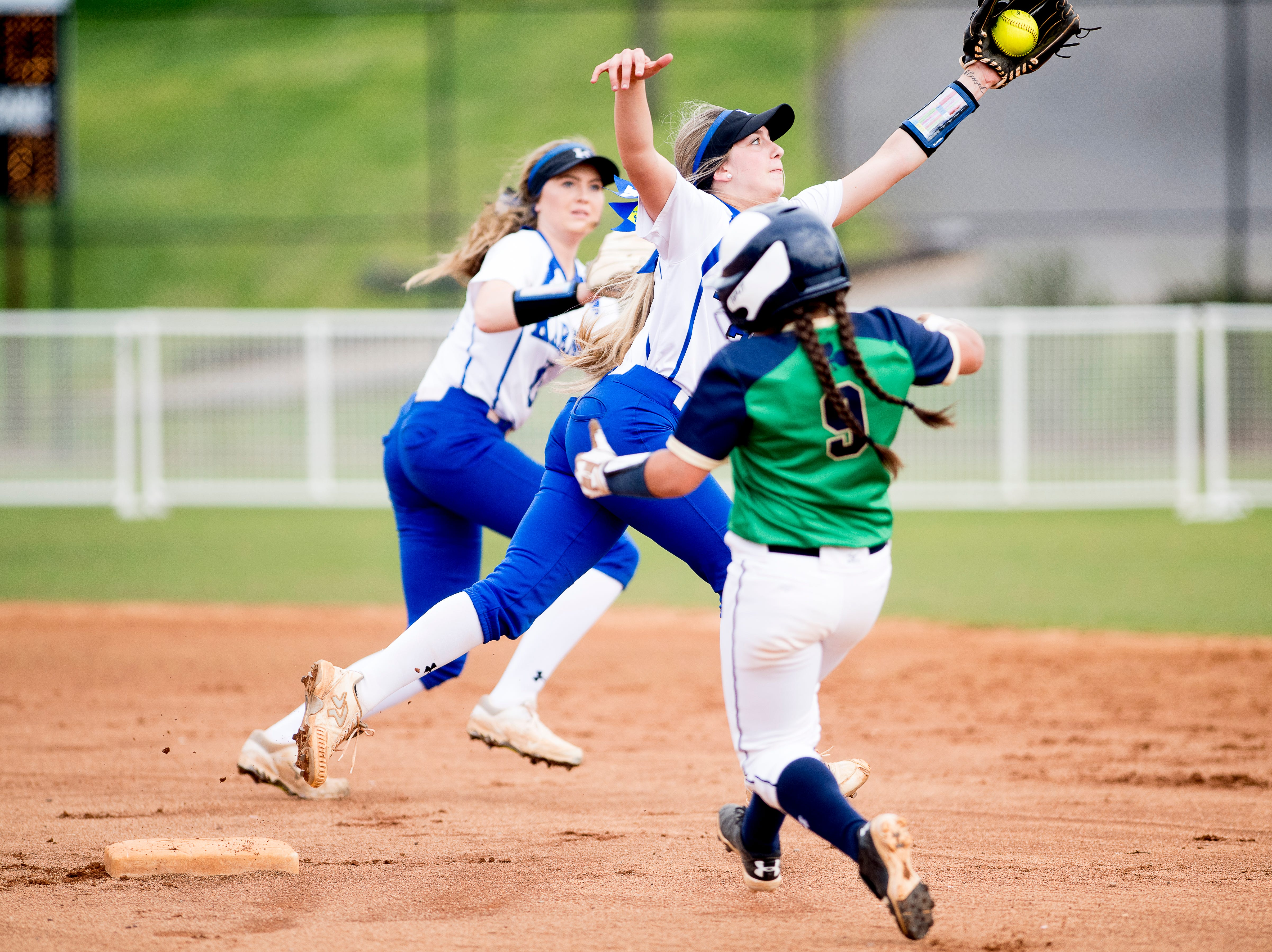 Karns' Jennifer Bezark (27) reaches for a throw to second as Catholic's Samantha Duffy (9) attempts a steal during a softball game between Catholic and Karns at Caswell Park in Knoxville, Tennessee on Friday, April 12, 2019.