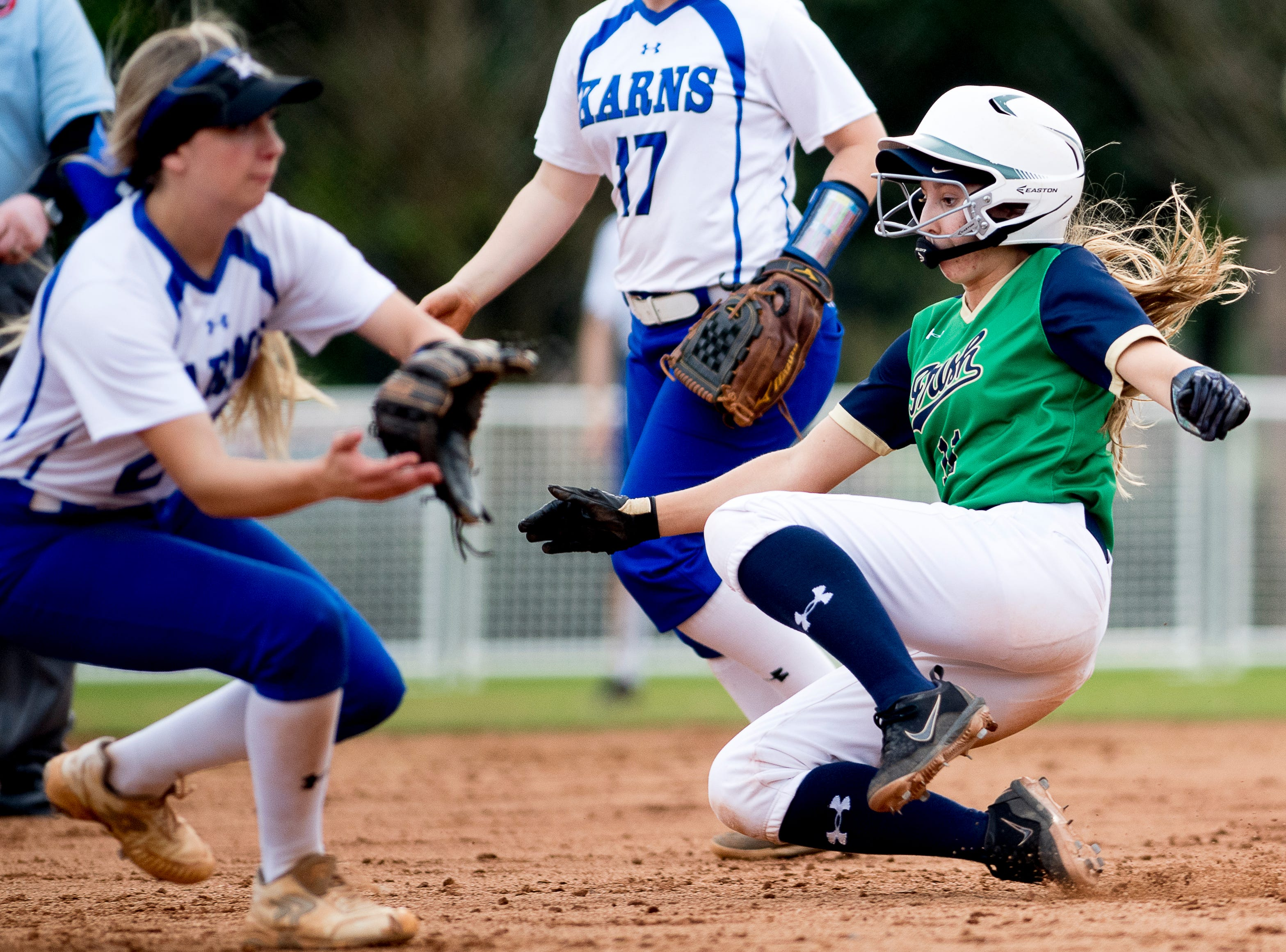 Catholic's Samantha Kaczmarek (11) slides into second as Karns' Jennifer Bezarek (27) catches the ball during a softball game between Catholic and Karns at Caswell Park in Knoxville, Tennessee on Friday, April 12, 2019.