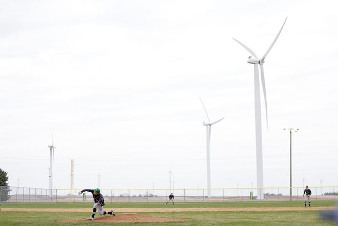 Windmills spin behind Taylor Varnado as he pitches during the fifth inning of a high school baseball game against Central Catholic, Wednesday, April 10, 2019, at Benton Central High School in Oxford.