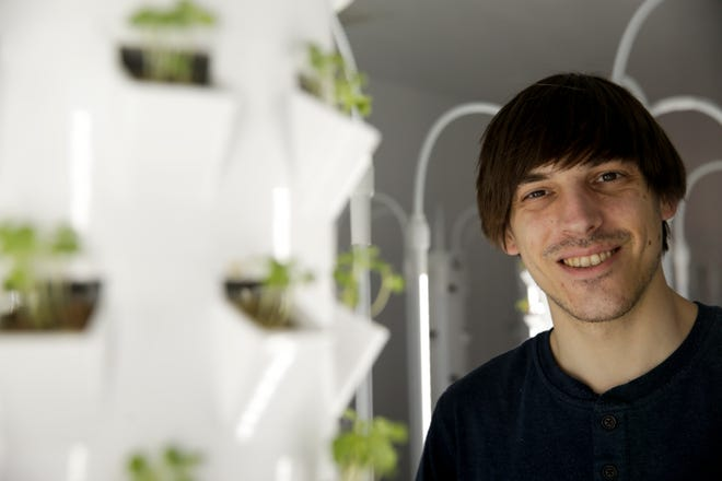 Austin Kasso poses for a portrait next to a vertical grow tower in the soon to open farmers market store with on-site produce cultivation, 525 Wabash ave, Friday, April 12, 2019, in Lafayette.