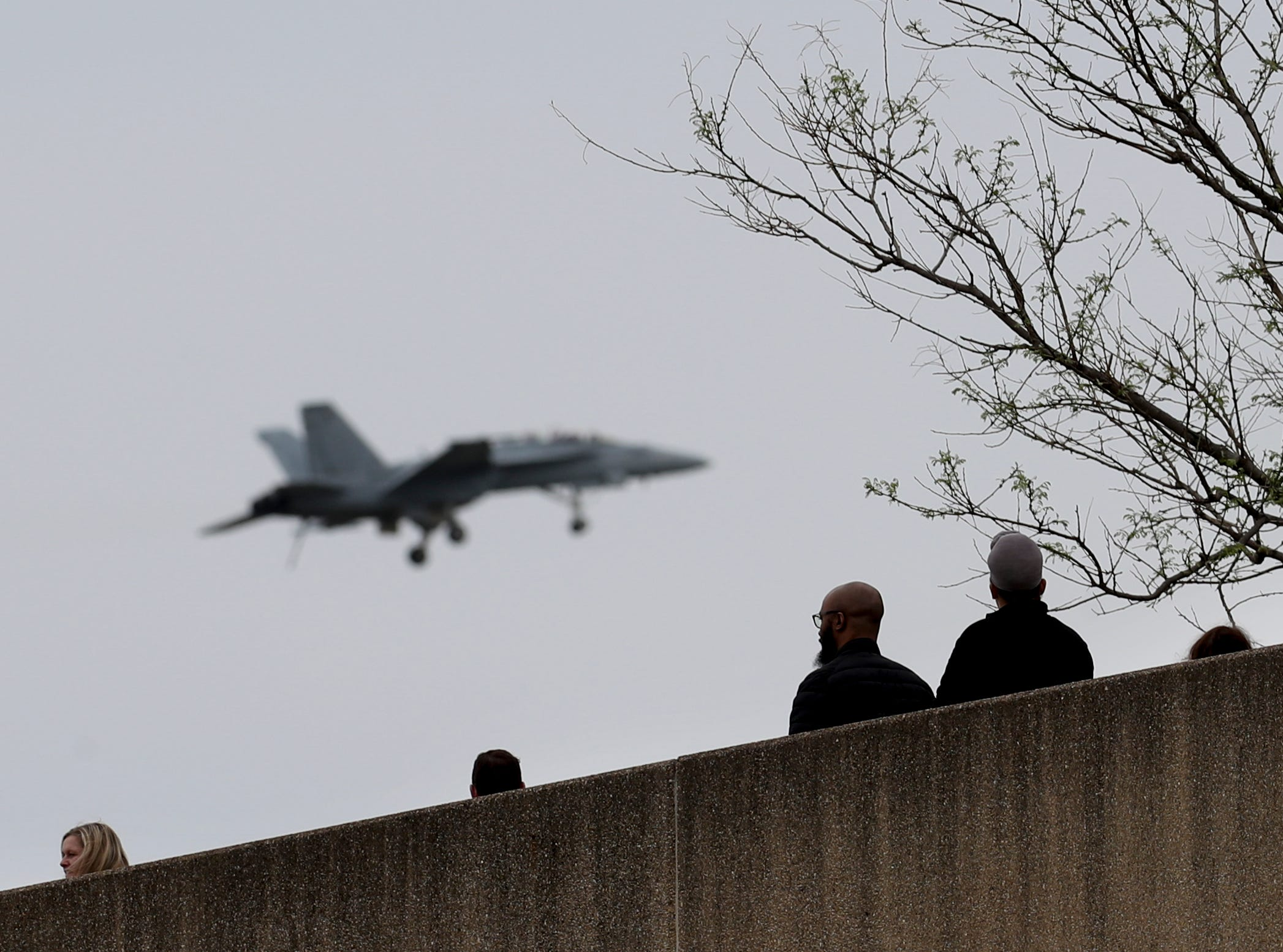 People on top of the Muhammad Ali Center watch airplanes practice in downtown Louisville on April 12 in preparation for the big Thunder Over Louisville airshow on Saturday.