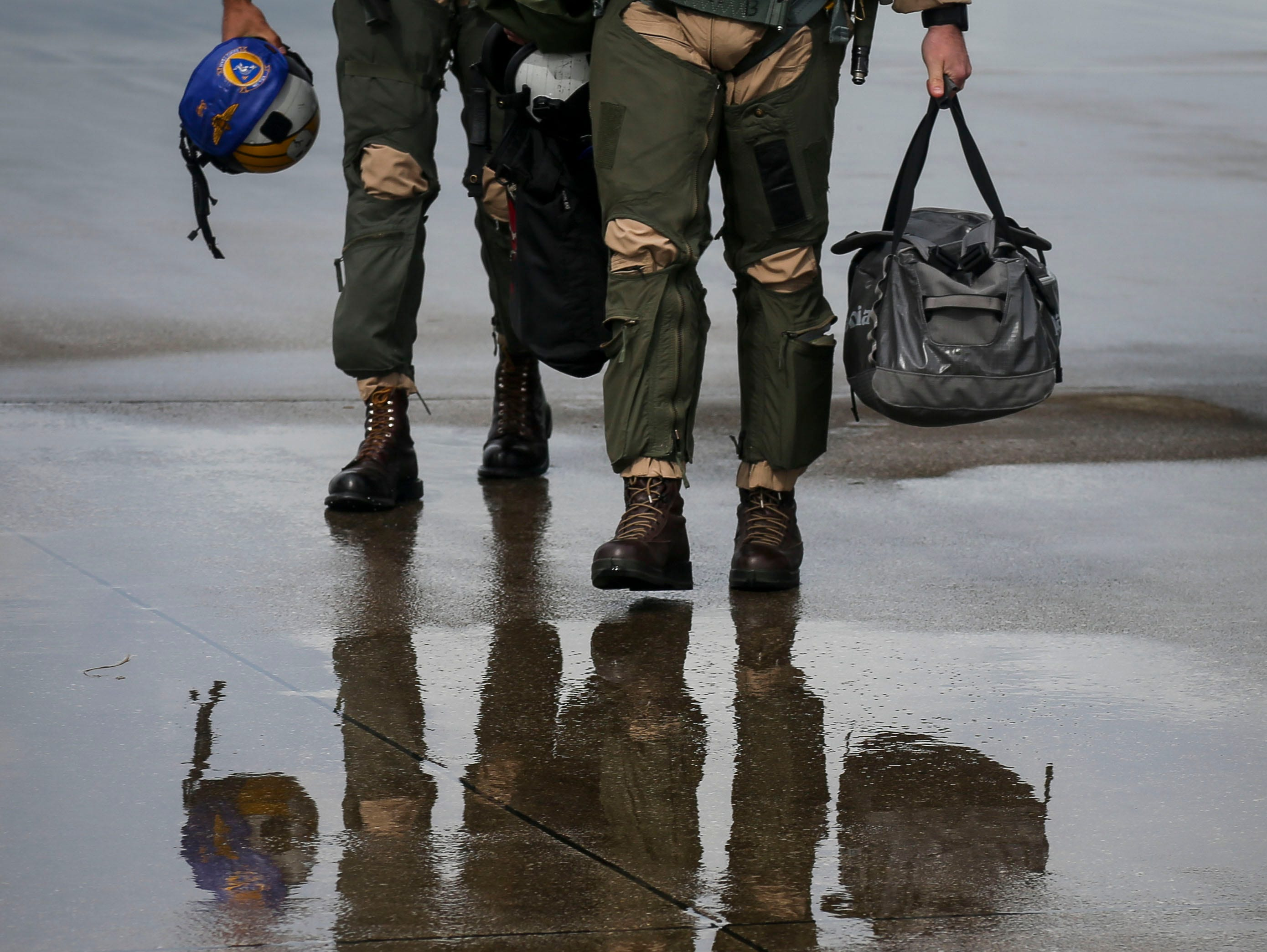 Lt. Chris Garner, left, and Lt. Jeff Mayer, right, walk off the runway after they navigated their F/A-18 Hornet, a twin-engine, supersonic combat jet, on the runway of the Kentucky Air National Guard ahead of practice for Thunder Over Louisville in Louisville, Ky. on Friday, April 12, 2019.