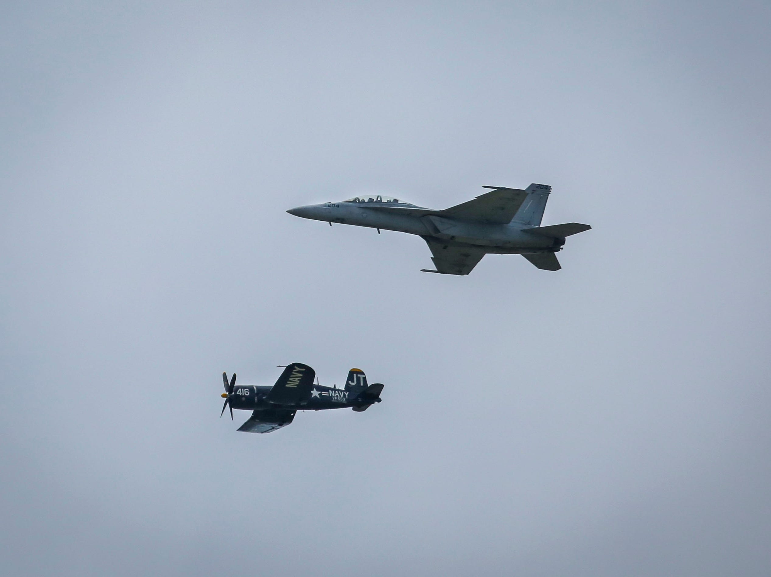 An F/A-18, right, and a Vought F4U, left, fly over the Ohio River during a practice ahead of Thunder Over Louisville in Louisville, Ky. on Friday, April 12, 2019.