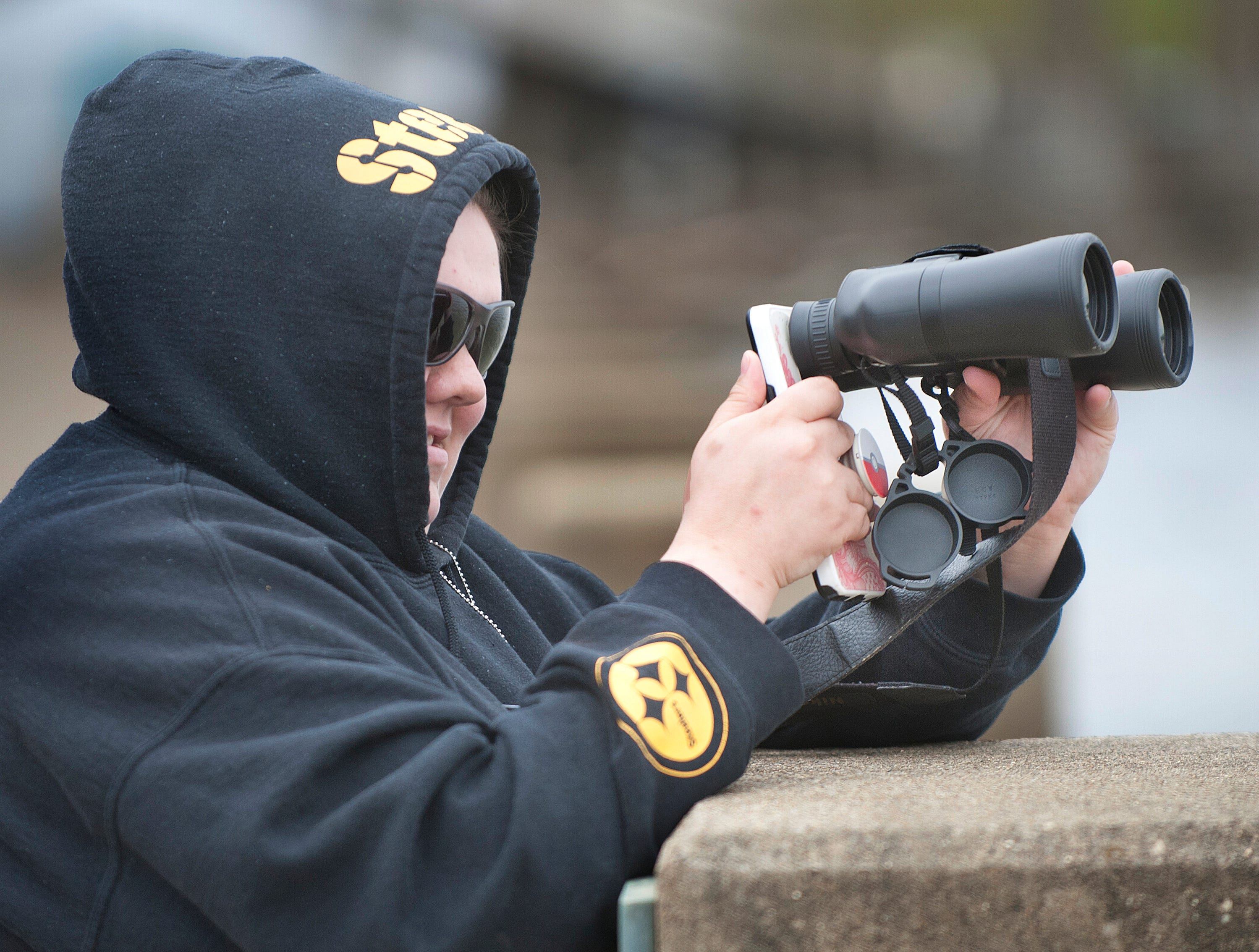 Destiny Smith of Valley Station put her phone camera up to a pair of binoculars to get close-ups of planes over the Ohio River rehearsing for the air show.12 April 2019