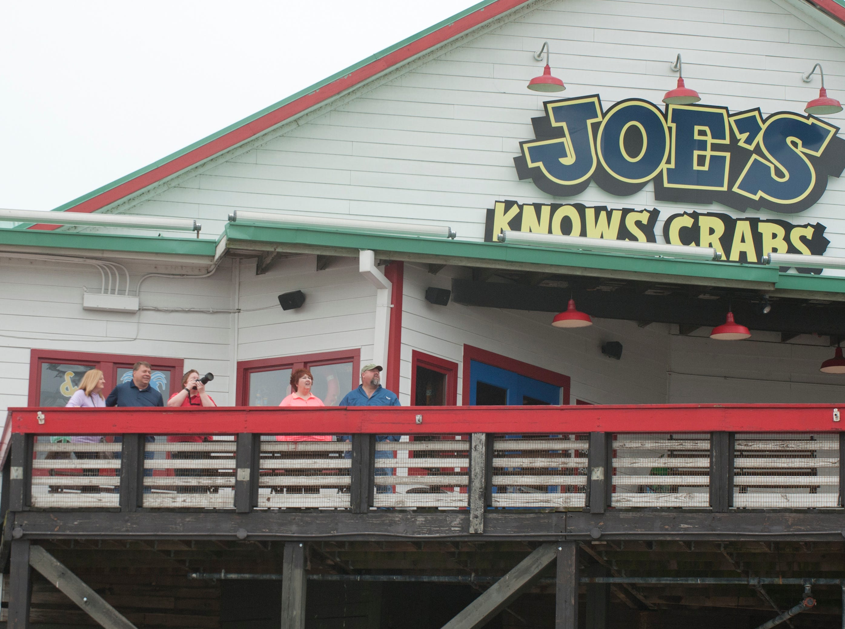 Spectators at Joe's Crab Shack watch the planes go by as they practice for the air show.12 April 2019