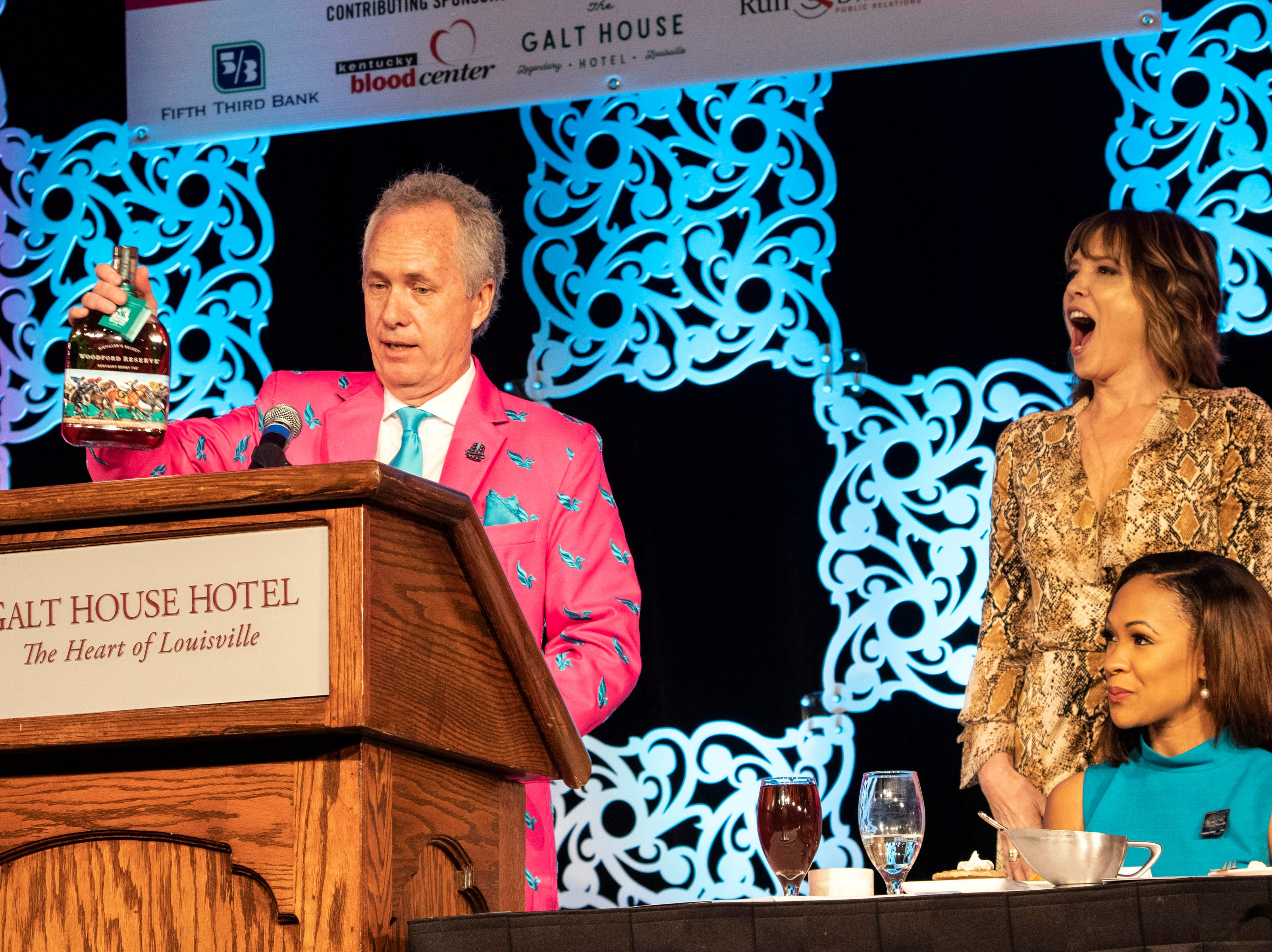 Hannah Storm reacts as Louisville mayor Greg Fischer presents her with several bourbons tied to the Kentucky Derby Festival during the annual They're Off! Luncheon on Friday. 4/12/19