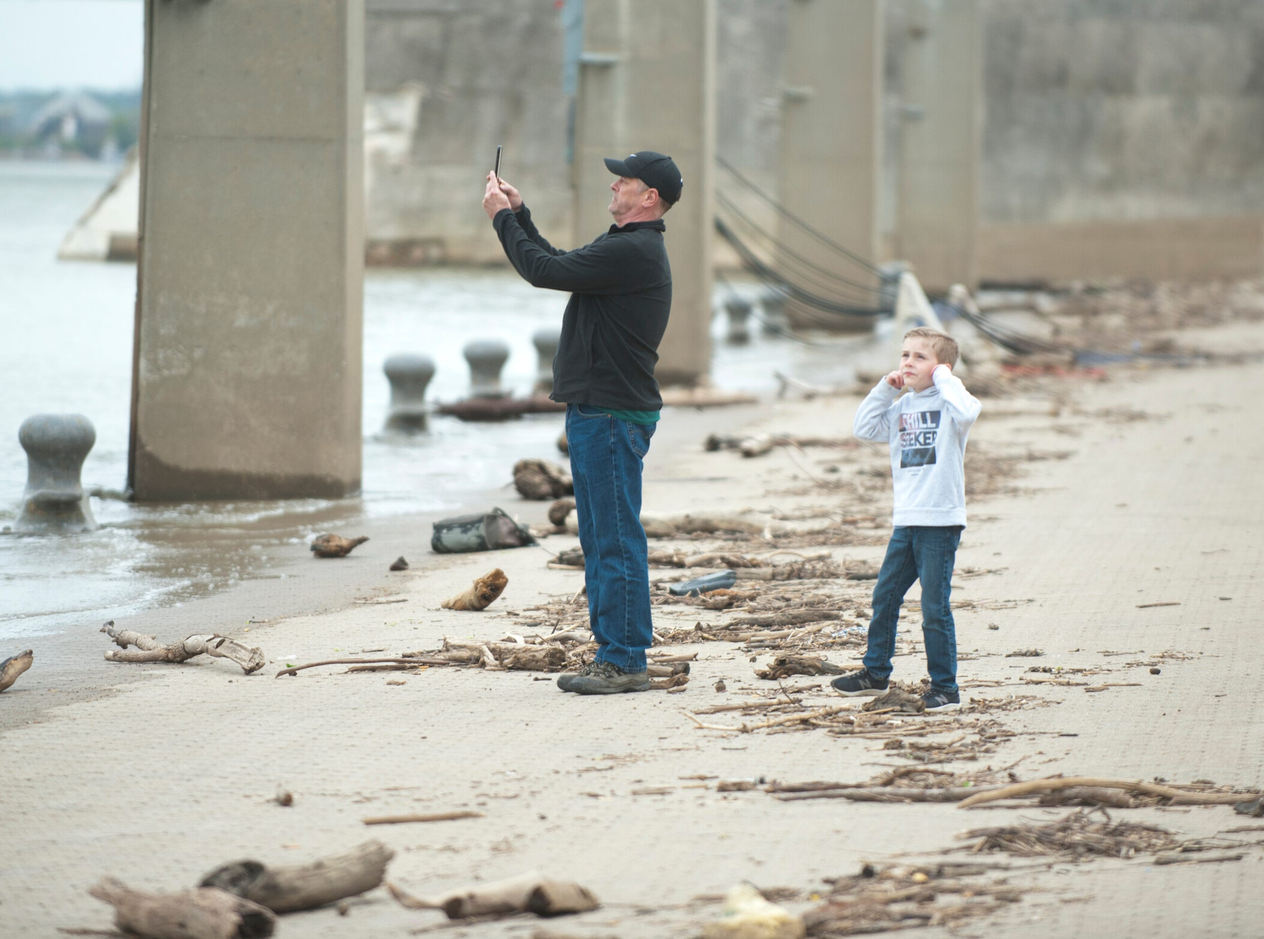 As a pilot above flies along the Ohio River,  Keith Jenkins of Shepherdsville, Ky., photographs it as he and his son, Nolan, age 6 (holding his ears) watch from the wharf between the Belle of Louisville and Joe's Crab Shack. Nolan was reacting to the noise of the plane's jets.12 April 2019