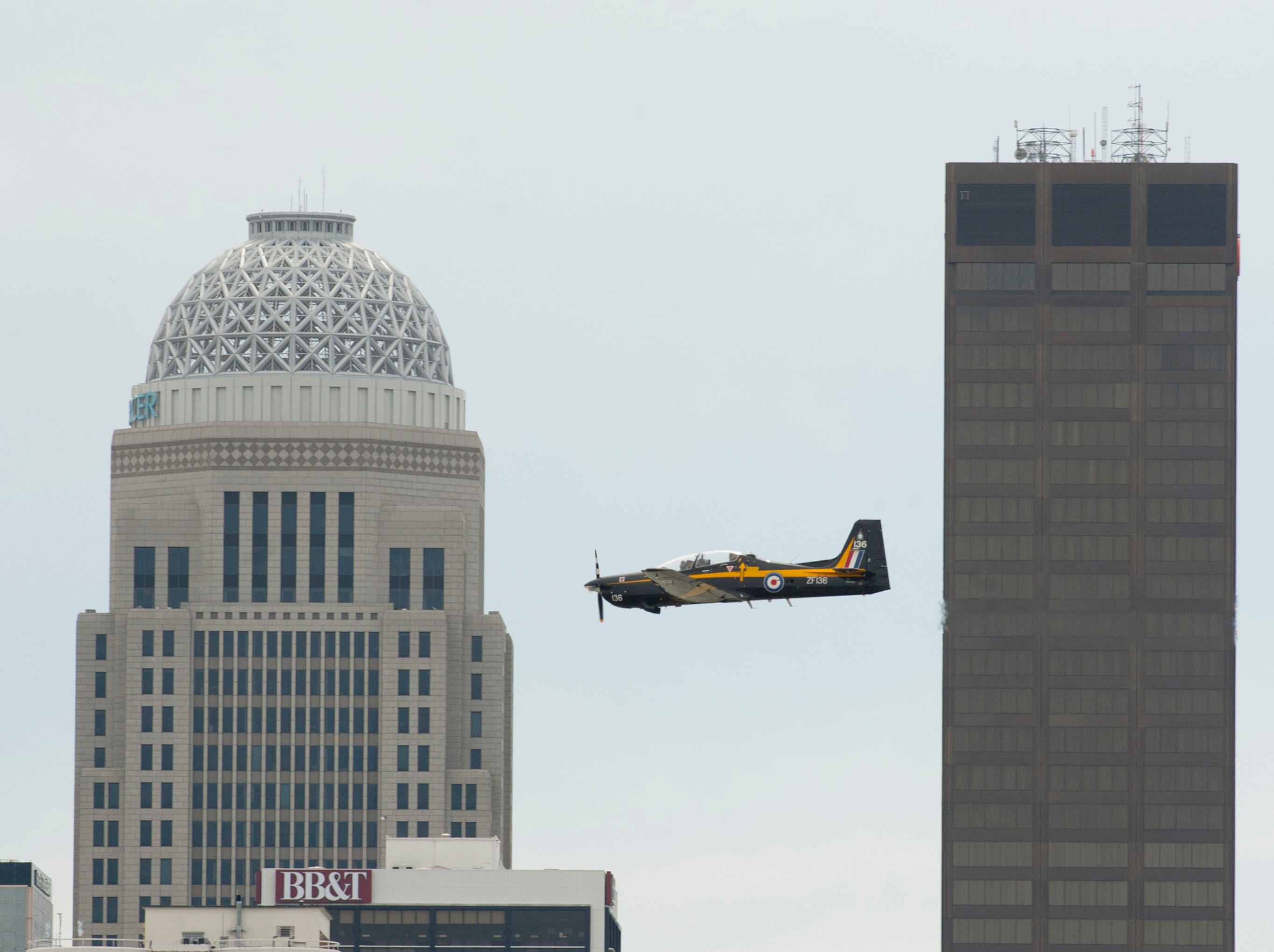 A plane flies past the Louisville downtown skyline, following the Ohio River as it practices for the airshow. 12 April 2019