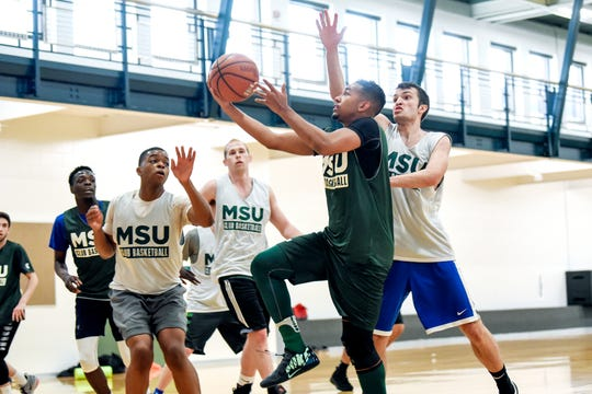 Robert Ray Jr., center, shoots a layup during a club basketball team practice on Friday, March 30, 2019, at IM Sports East on the Michigan State University campus in East Lansing.