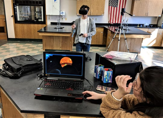 Manitowoc Lincoln High School astronomy student Casey Jessel heads towardthe sun while Houa Vang helps run the VR software.