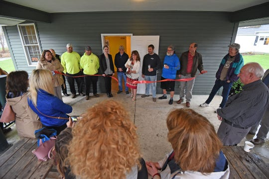Bellville mayor Teri Brenkus cuts the ribbon Friday morning during a ceremony celebrating the improvements to the Bellville bike depot.