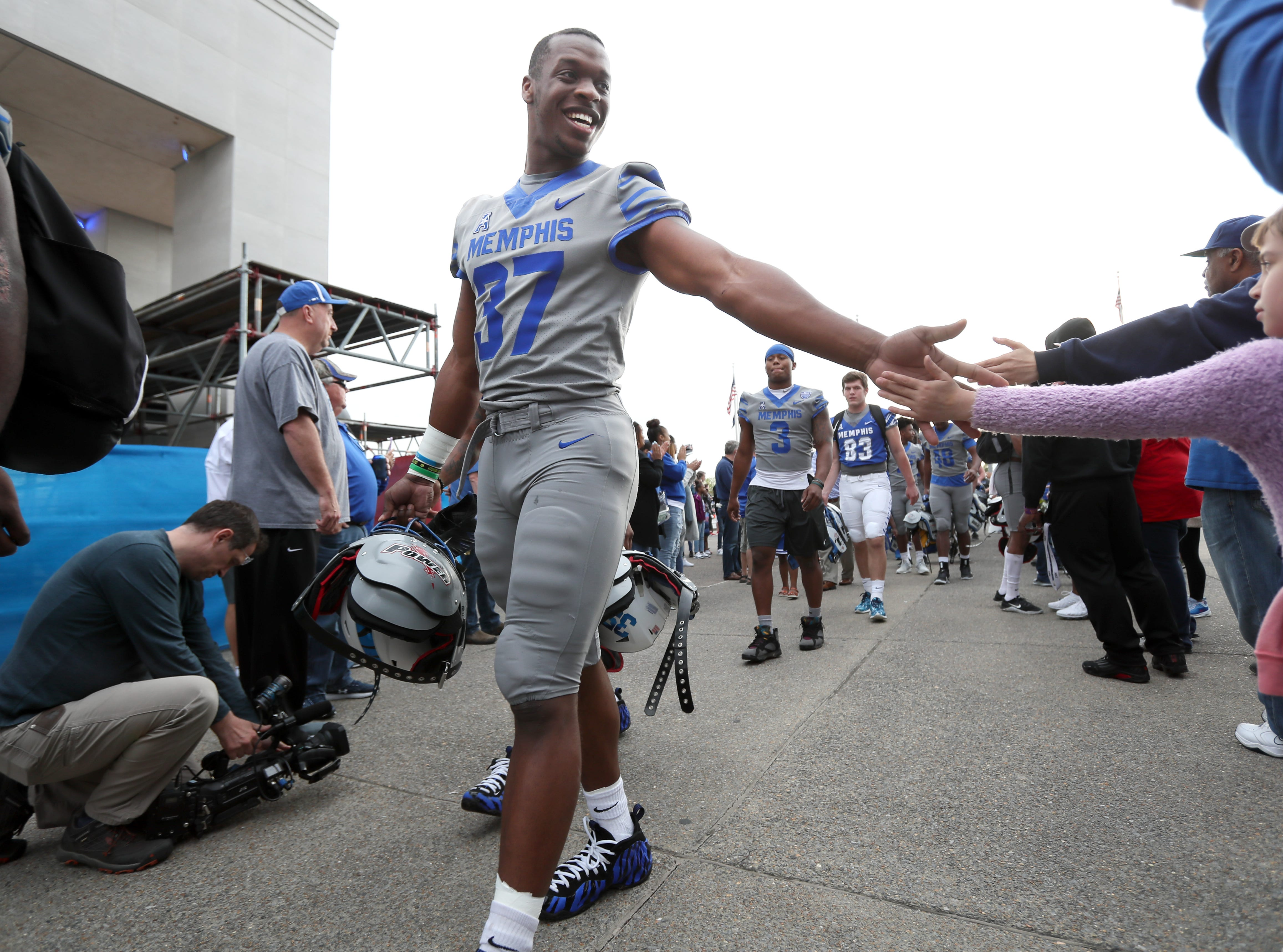 Tigers linebacker Jaylon Allen greets fans before their 'Friday Night Stripes' spring game at Liberty Bowl Memorial Stadium on Friday, April 12, 2019.