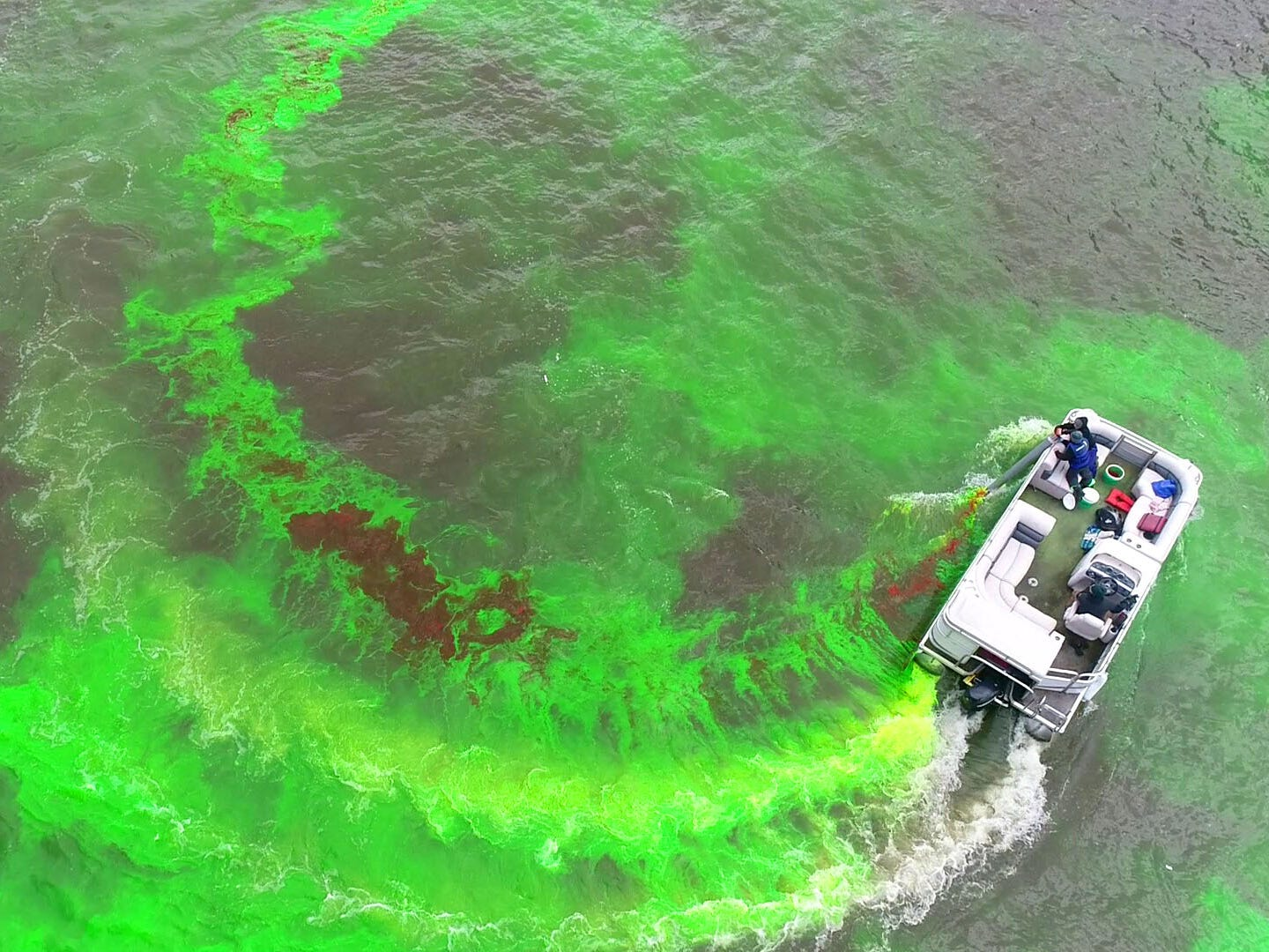 A boat dumps green dye near the West  McKinley Avenue bridge. Milwaukee celebrated the start of the Milwaukee Bucks in the NBA Playoffs by dyeing the Milwaukee River green in Milwaukee on Friday, April 12, 2019. The Bucks partnered with the city and the state Department of Natural Resources to dye the river green and throw a kickoff party near Fiserv Forum.