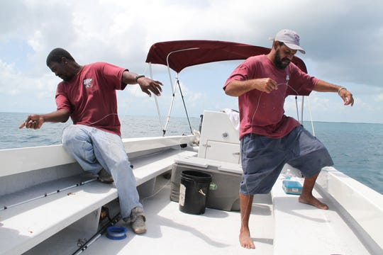 Belizean fishing guides Randolph (left) and Kenrick use hand lines to fish for snapper, jacks and other species in the Caribbean waters east of Belize City, Belize.