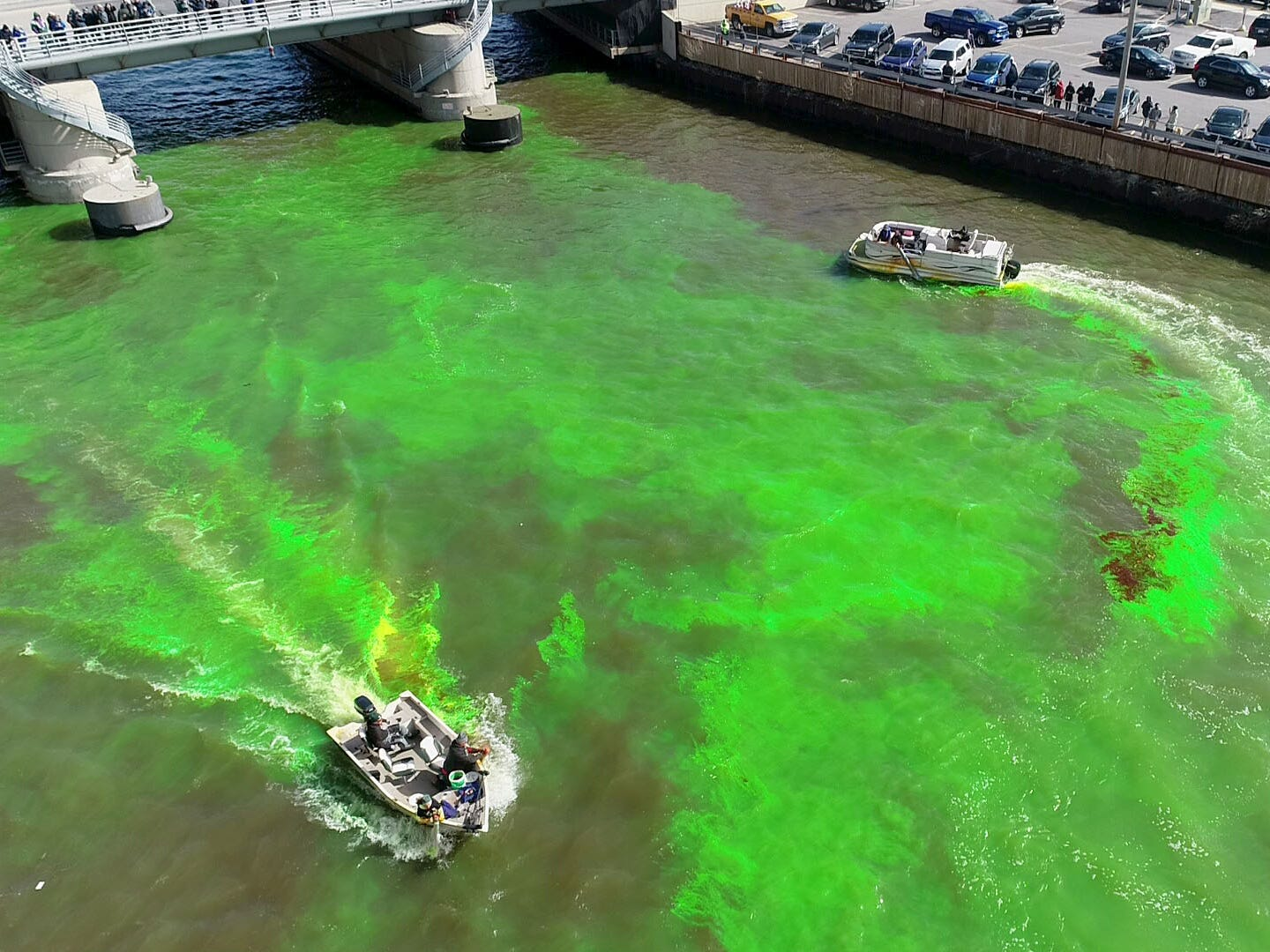 A boat dumps green dye while another swirls it around near the West  McKinley Avenue bridge. Milwaukee celebrated the start of the Milwaukee Bucks in the NBA Playoffs by dyeing the Milwaukee River green in Milwaukee on Friday, April 12, 2019. The Bucks partnered with the city and the state Department of Natural Resources to dye the river green and throw a kickoff party near Fiserv Forum.