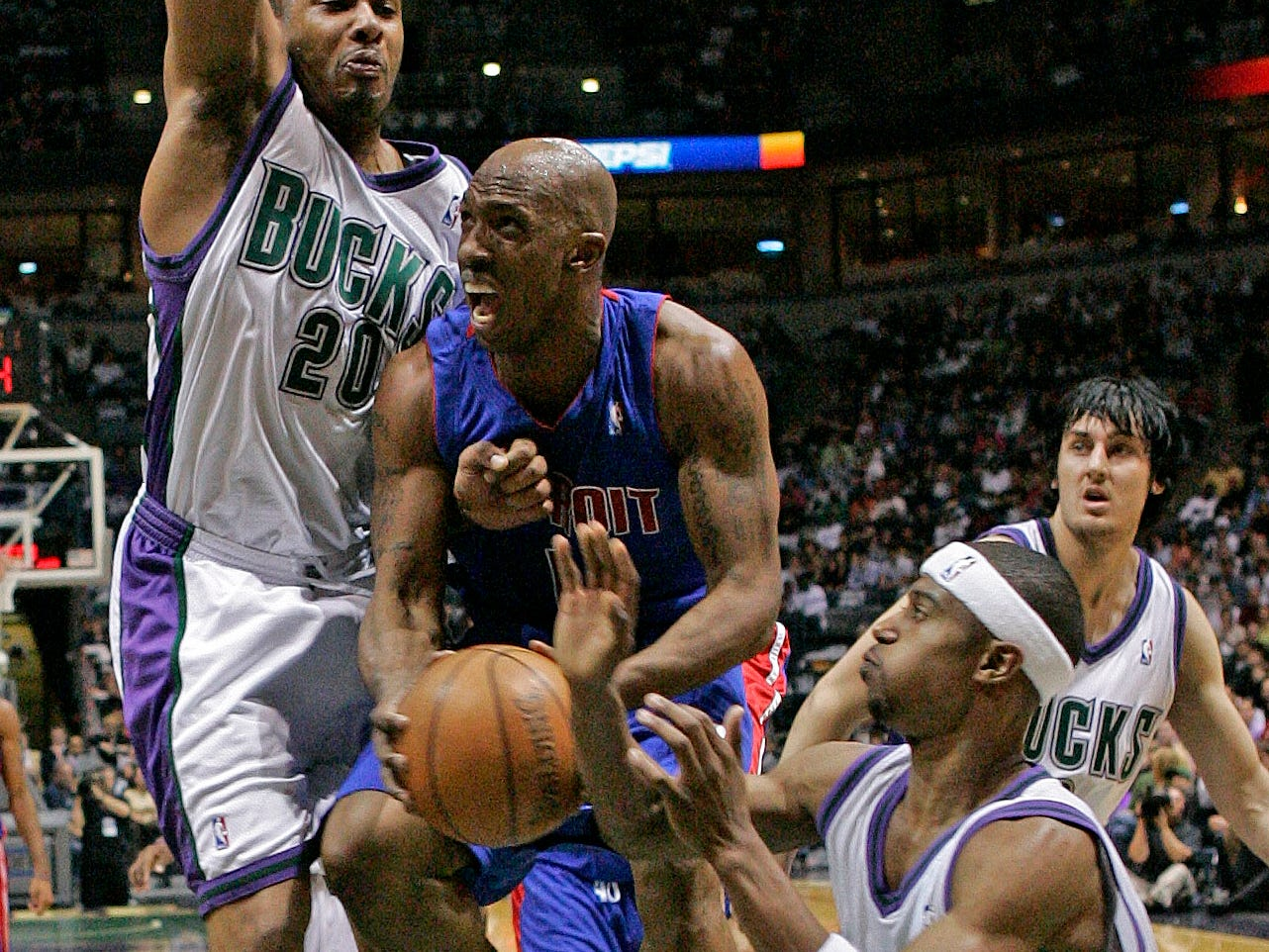 2006: Detroit Pistons' Chauncey Billups (center) is fouled as he drives to the basket between Milwaukee Bucks' Jamaal Magloire (left), T.J. Ford (bottom) and Andrew Bogut during the first quarter of Game 3 of the Eastern Conference playoff's first round at the Bradley Center on April 29, 2006. The Bucks won, 124-104, but it was their only victory in the series; the Pistons eliminated Milwaukee in five games.