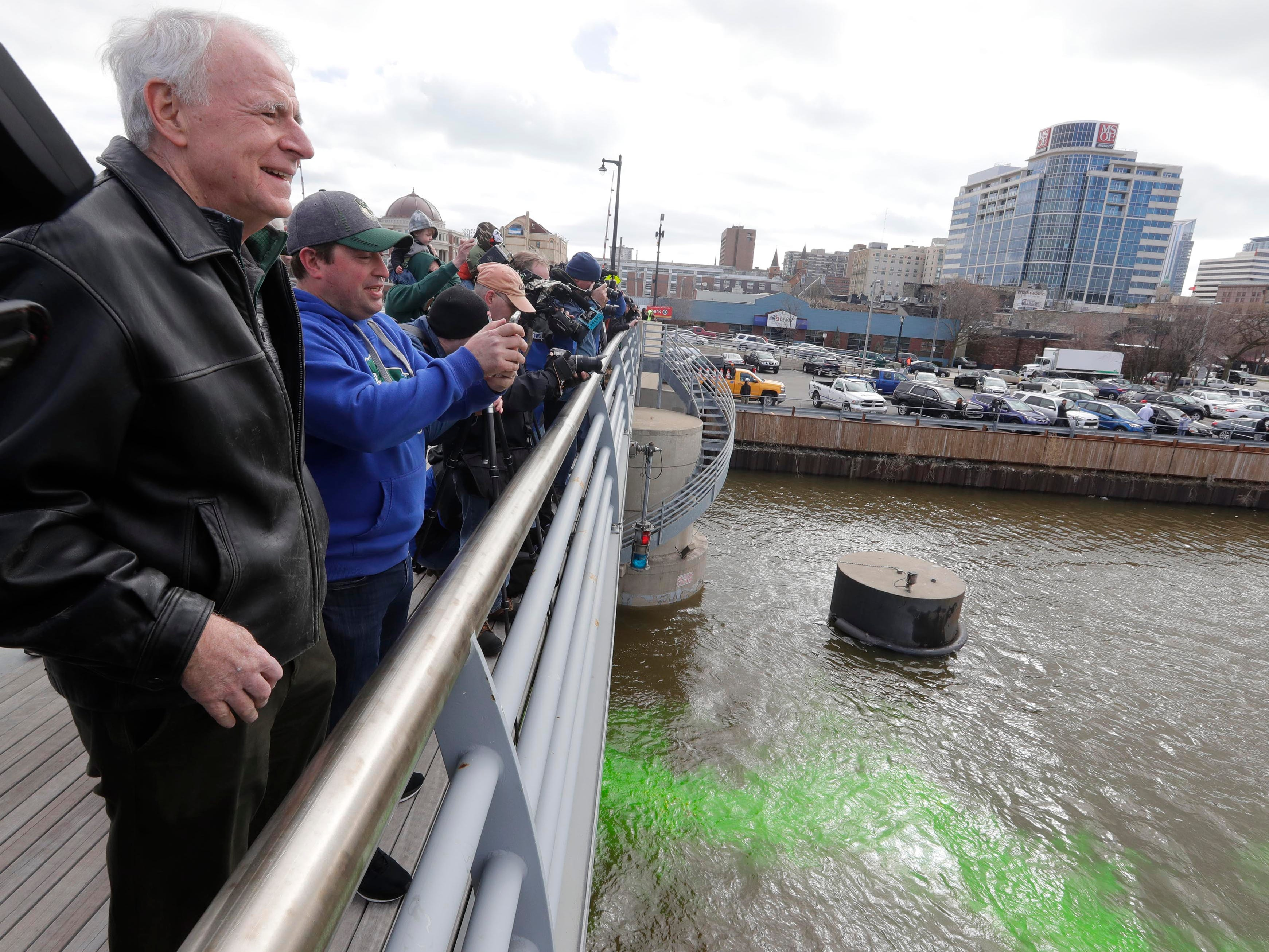 Mayor Barrett and Bucks President Peter Feigin take their own pics of the river turning green. Excitement over the Milwaukee Bucks heading into the NBA playoffs this weekend is enough to turn the Milwaukee River a bright shade of green. Milwaukee Bucks president Peter Feigin and Milwaukee Mayor Tom Barrett watch as boats drop harmless green powder into the Milwaukee River near McKinley to celebrate the Milwaukee Bucks playoffs which begin Sunday.