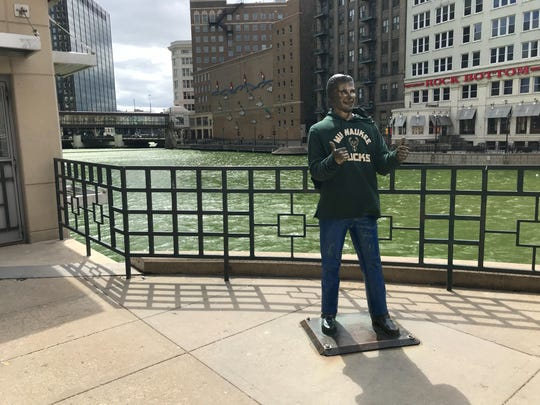 The Bronze Fonz is sporting a Milwaukee Bucks sweatshirt in front of a green-colored Milwaukee River.
