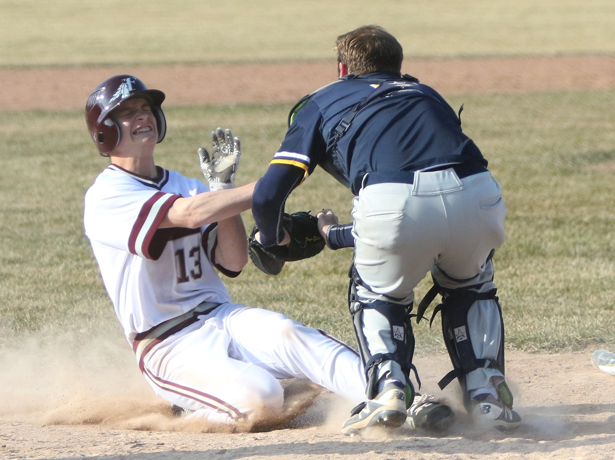 A Menomonee Falls base runner is tagged out at home plate in a game against Marquette on April 5, 2019.