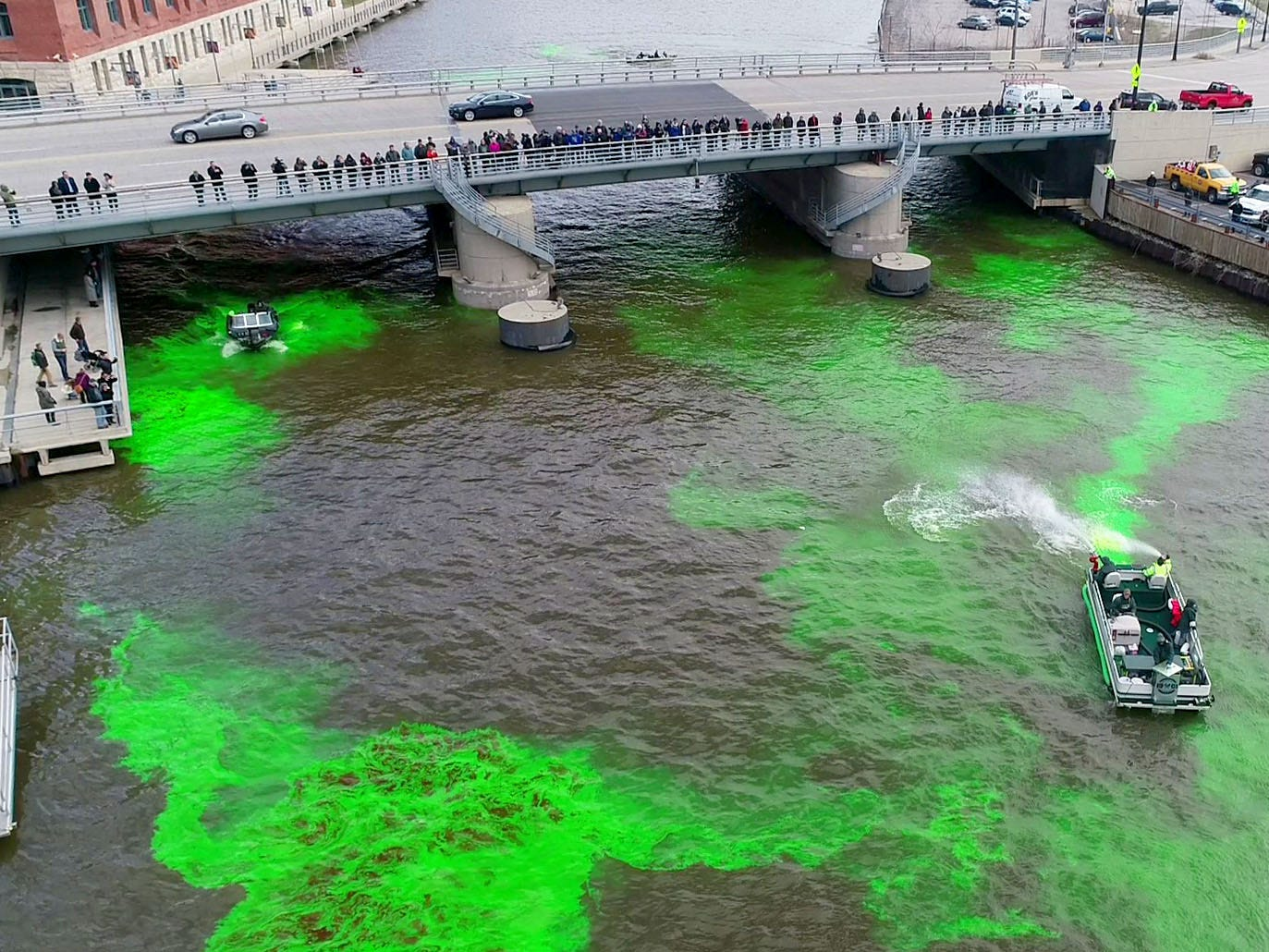 A boat swirls around the green dye near the West  McKinley Avenue bridge. Milwaukee celebrated the start of the Milwaukee Bucks in the NBA Playoffs by dyeing the Milwaukee River green in Milwaukee on Friday, April 12, 2019. The Bucks partnered with the city and the state Department of Natural Resources to dye the river green and throw a kickoff party near Fiserv Forum.