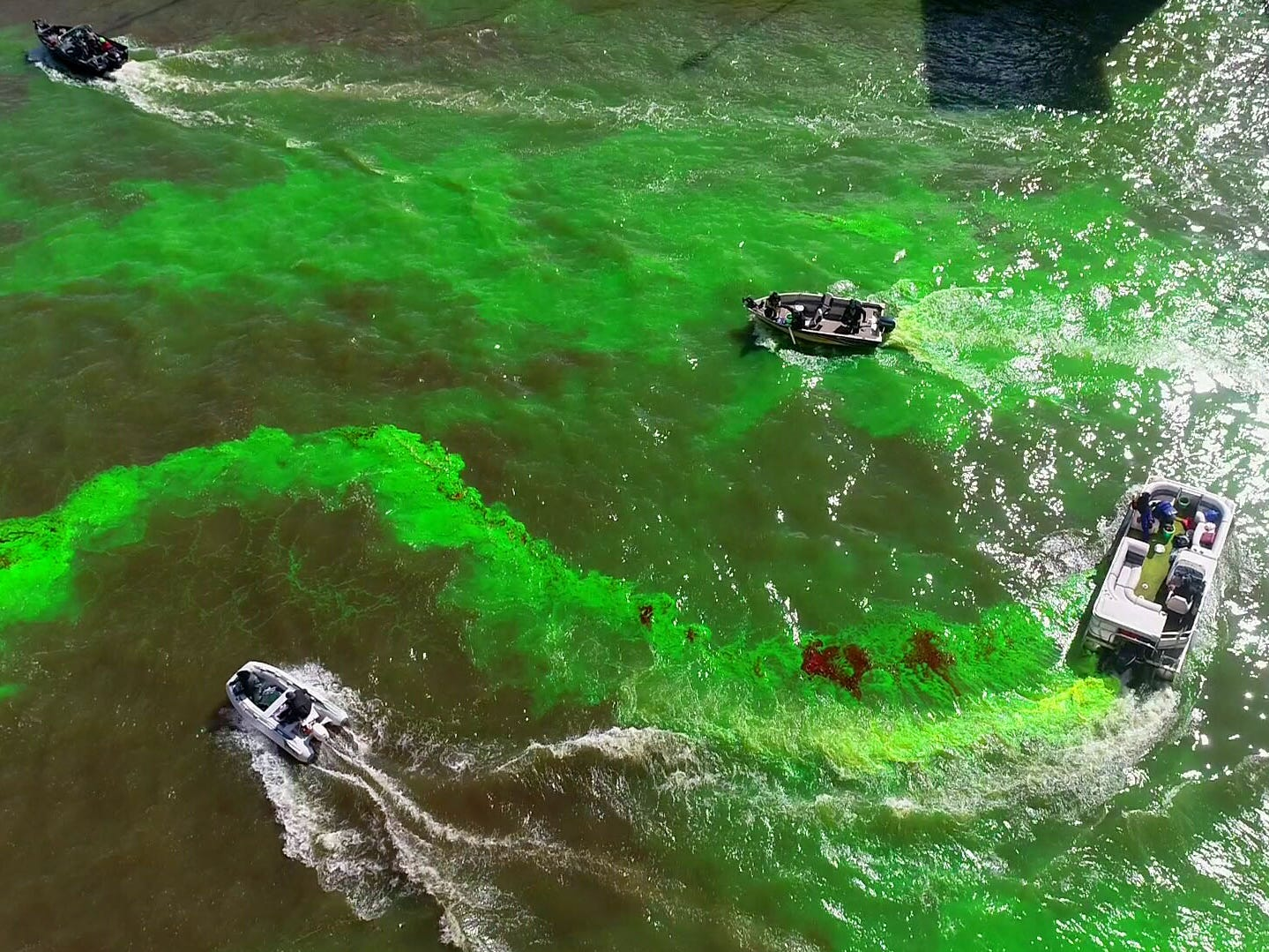 A boat dumps green dye while other boats swirl it around near the East Juneau Avenue bridge. Milwaukee celebrated the start of the Milwaukee Bucks in the NBA Playoffs by dyeing the Milwaukee River green in Milwaukee on Friday, April 12, 2019. The Bucks partnered with the city and the state Department of Natural Resources to dye the river green and throw a kickoff party near Fiserv Forum.