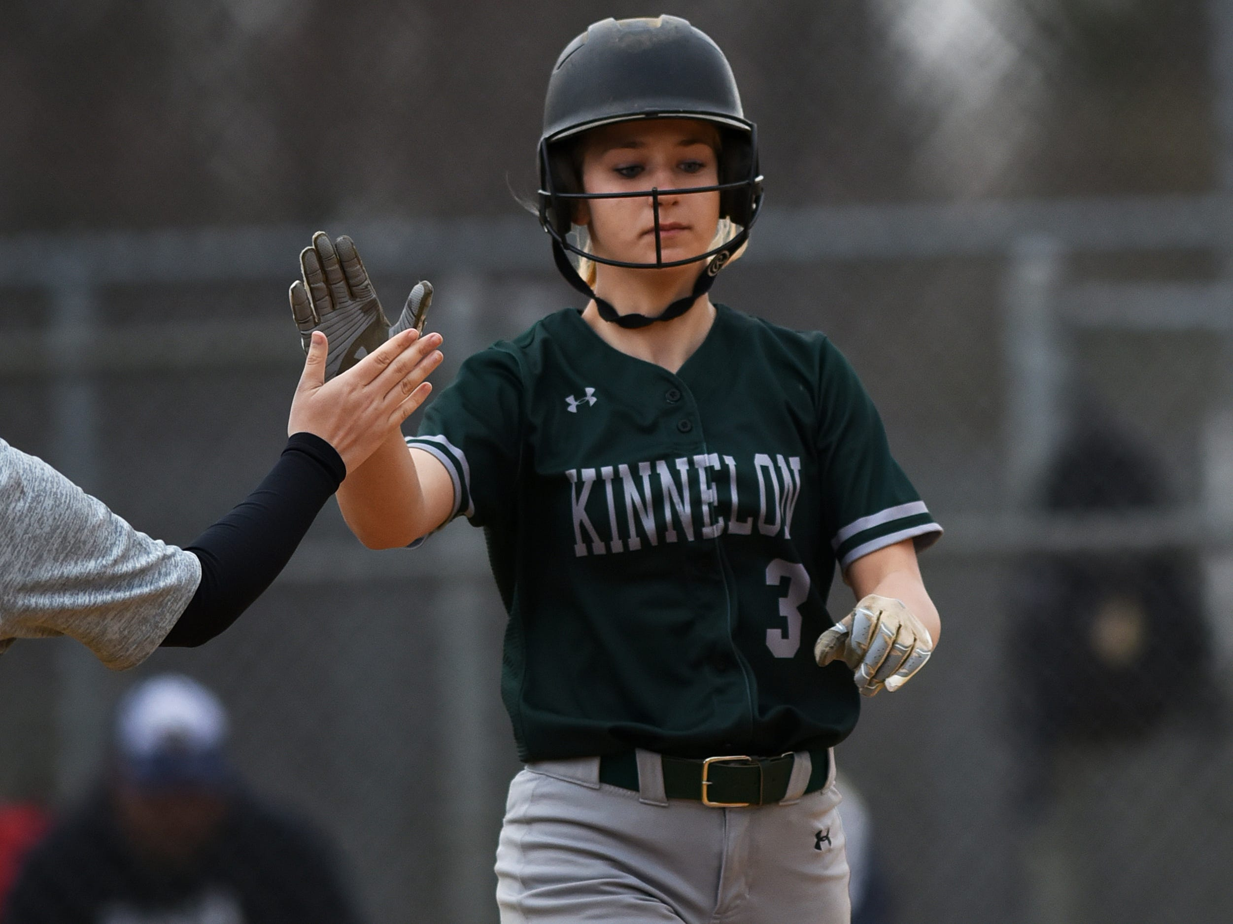 Pequannock at Kinnelon softball game in Kinnelon on Friday April 12, 2019. K#3 Jess Handzo gets a high five as she makes her way to first base.