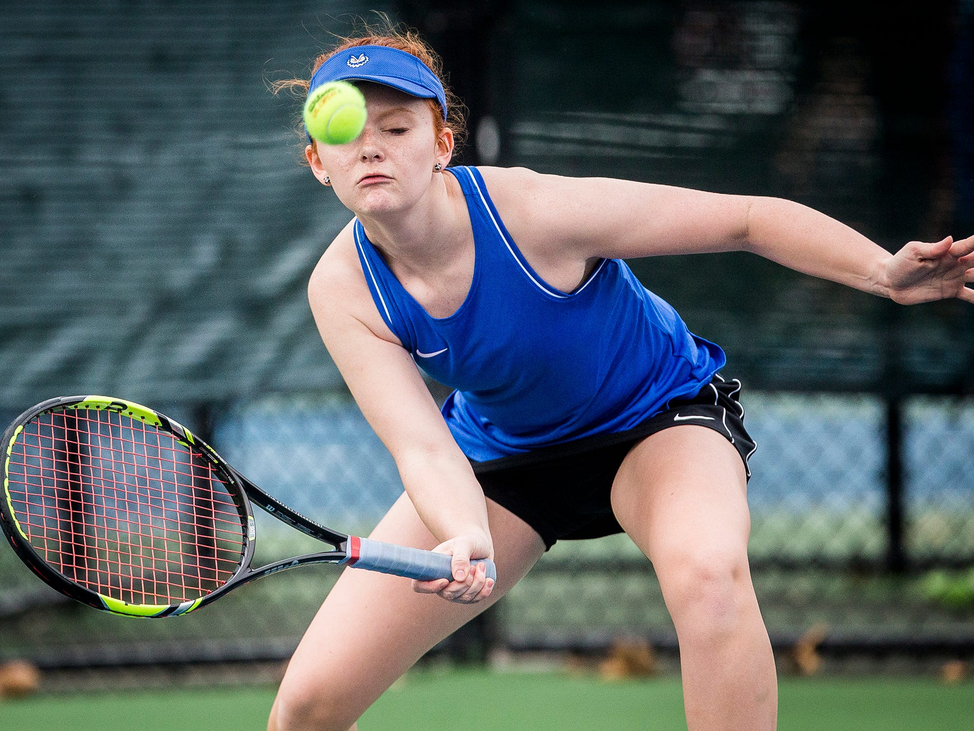 Burris' Isabelle Berhman returns a hit from Central's Katie Hunter during their singles match at Ball State Thursday, April 11, 2019.