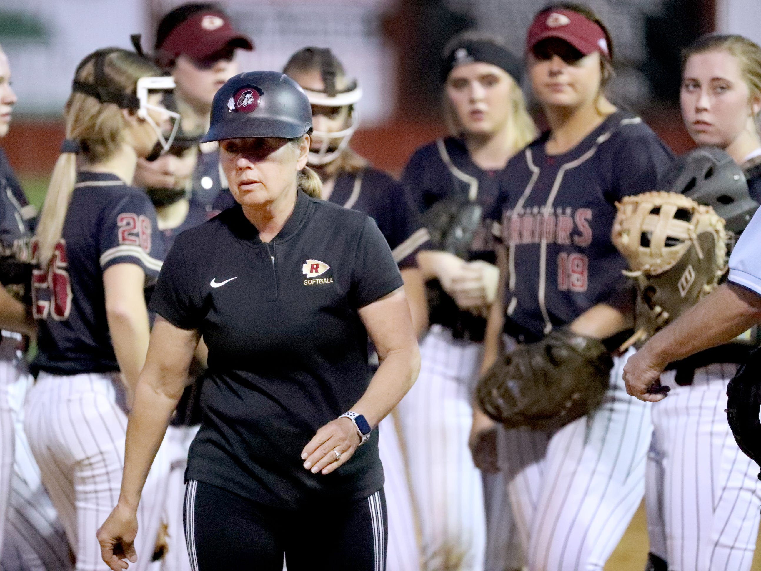Riverdale's head coach Christy Bingham talks with her players on the field as the bases are loaded during the game against Siegel on Thursday April 11, 2019, at Riverdale.