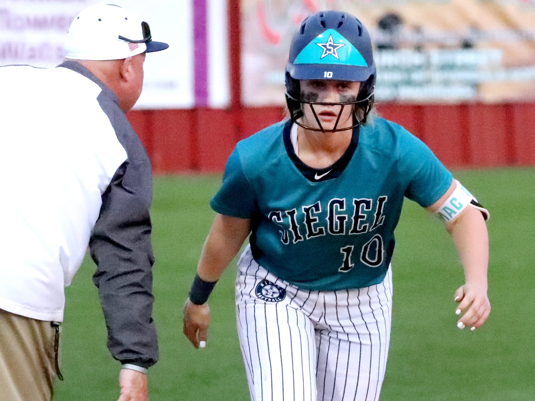 Siegel's head coach Shawn Middleton congratulates Siegel's Caitlyn McCrary (10) for a homer as she rounds third base during the game against Riverdale on Thursday April 11, 2019, at Riverdale.