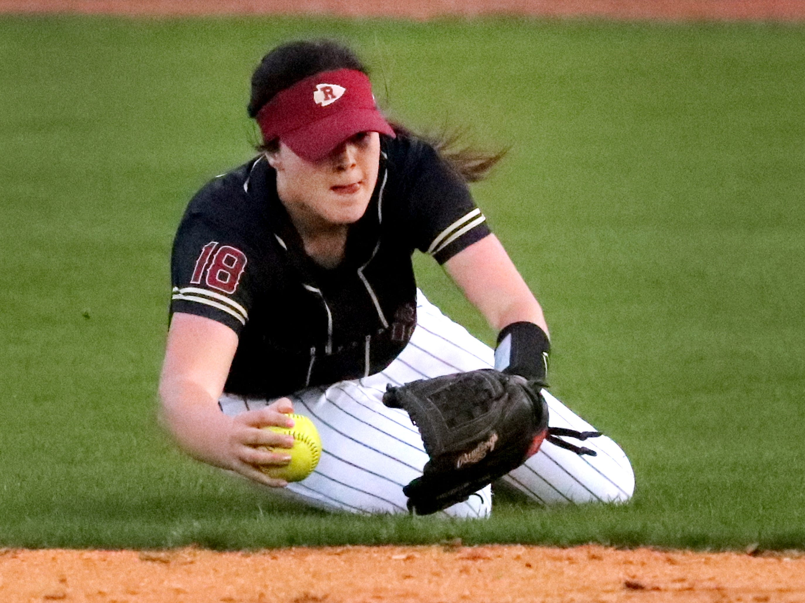 Riverdale's Sydney Williams (18) makes a catch and holds onto it as she falls to the ground in the outfield during the game against Siegel on Thursday April 11, 2019, at Riverdale.