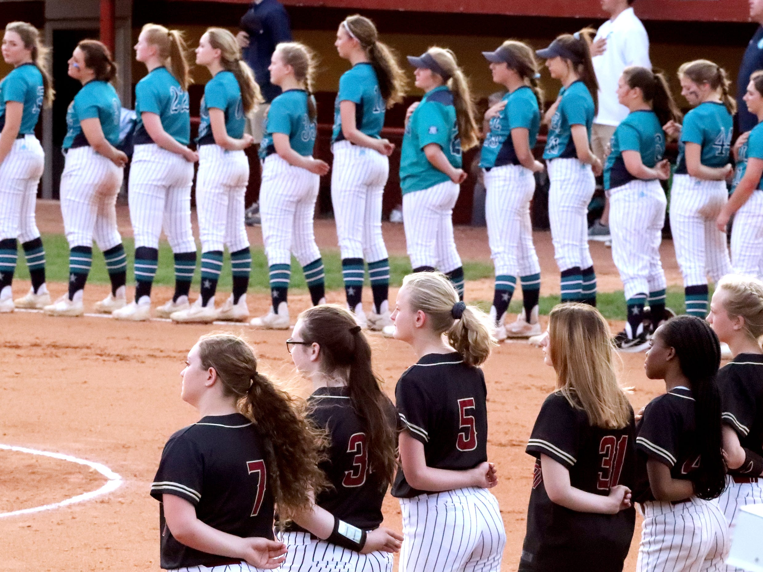 Siegel and against Riverdale players stand for the anthem before the start of the softball game on Thursday April 11, 2019, at Riverdale.