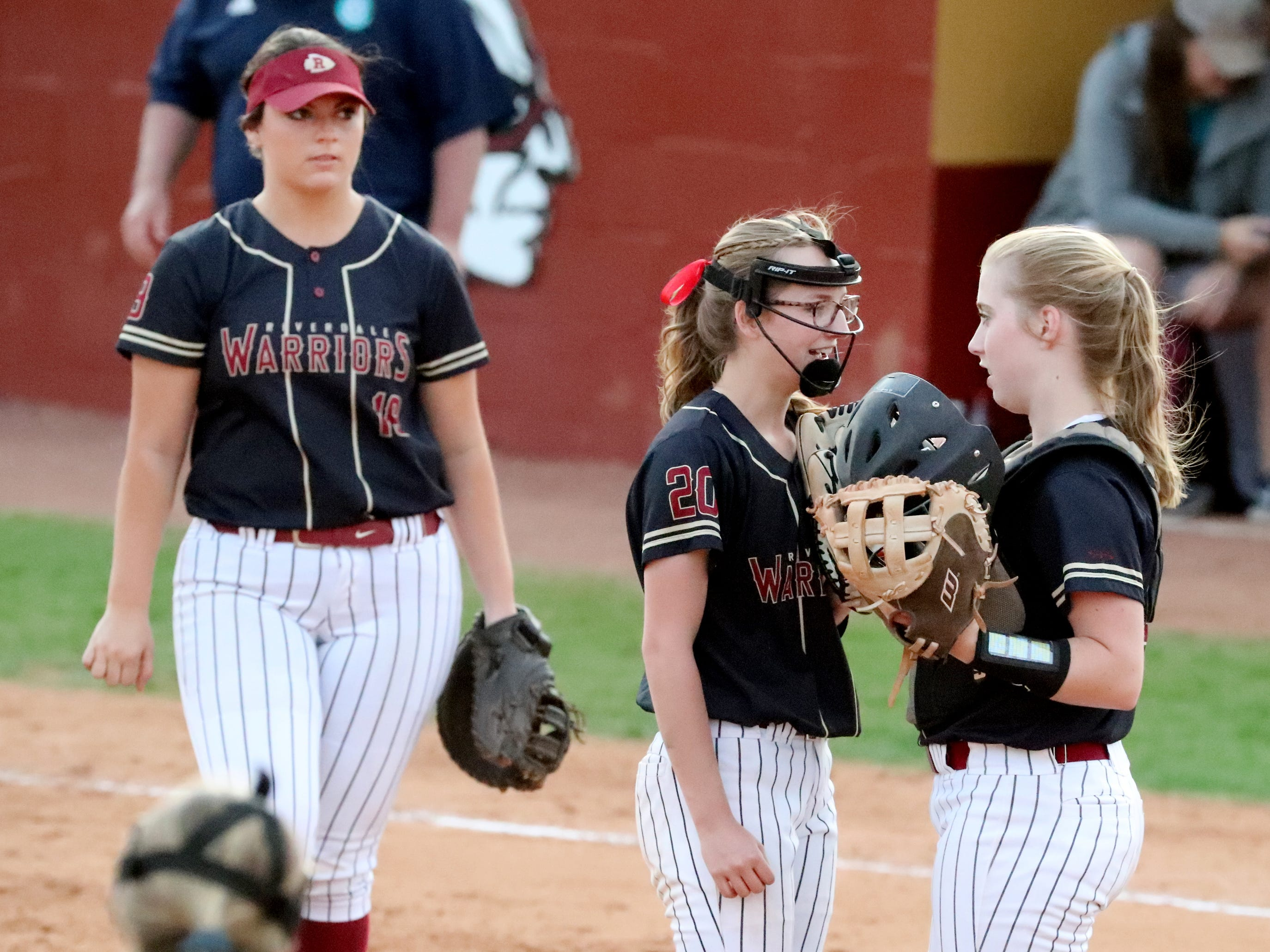 Riverdale's pitcher Alexis Chapman (20) talks with the catcher Riverdale's Kendall Forsythe (21) during the game against Siegel as Riverdale's Sarah Margaret Lowe (19) walks to the pitcher's circle on Thursday April 11, 2019, at Riverdale.