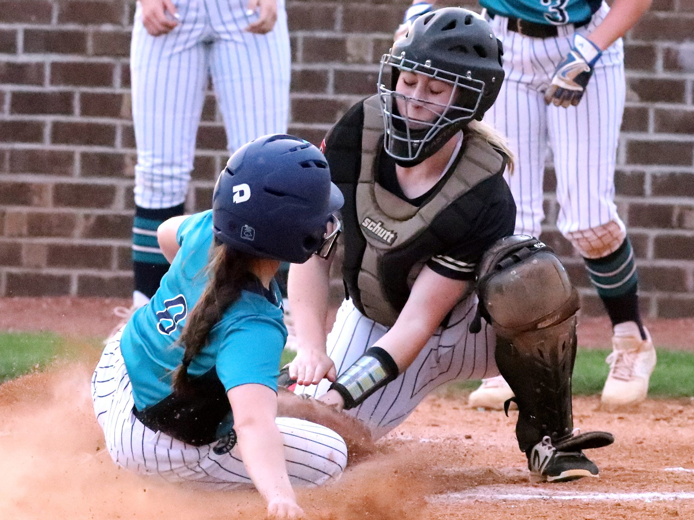 Riverdale's catcher Kendall Forsythe (21) tags out Siegel's Hope Keeeton (6) as she slides into home plate on Thursday April 11, 2019, at Riverdale.