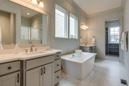 Master baths features tiled showers and freestanding tubs in homes built by Celebration Homes in Durham Farms.