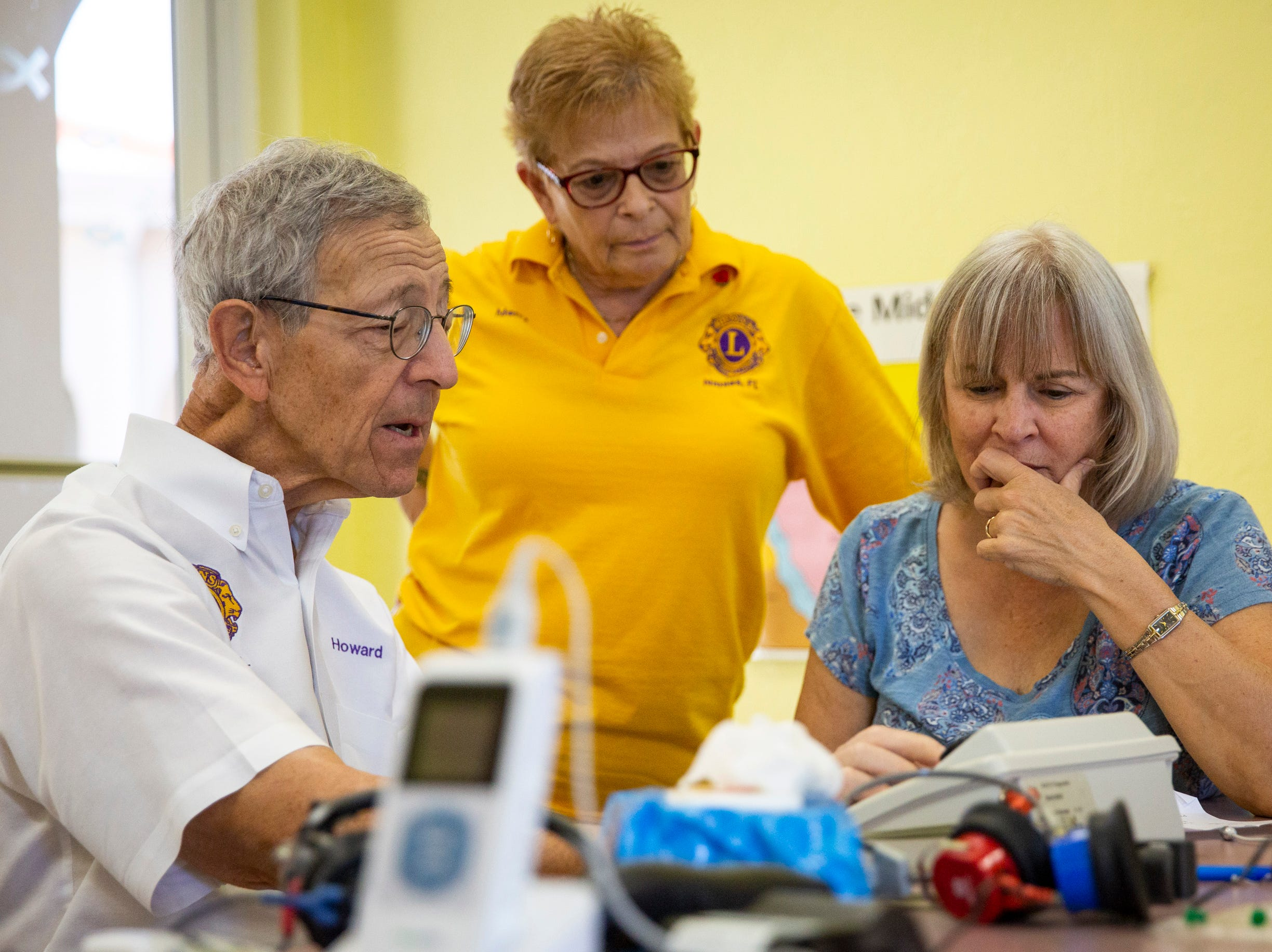 Dr. Howard Freedman, left, shows Merry Hovey, center, and Diane Leone, right, how to use a machine to test hearing at Grace Lutheran Preschool in Naples on Friday, April 12, 2019. Freedman is a retired pediatric eye doctor and now spends his time working with the Naples Lions Club to provide free screenings to children and adults in the area.