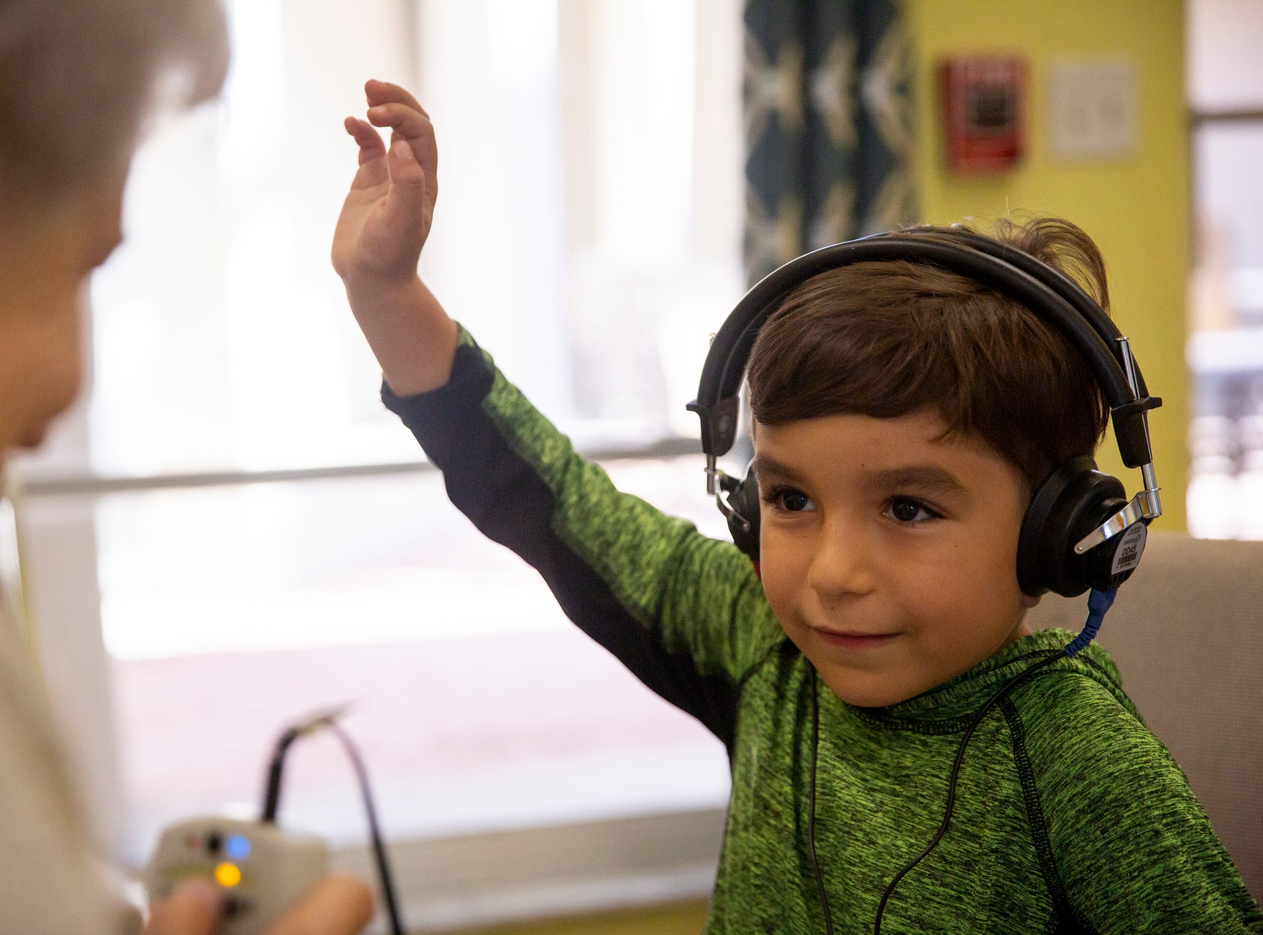 Daniel Dremi, 5, raises his hand to signal that he hears a noise coming through his headphones while he gets his hearing tested at Grace Lutheran Preschool in Naples on Friday, April 12, 2019.