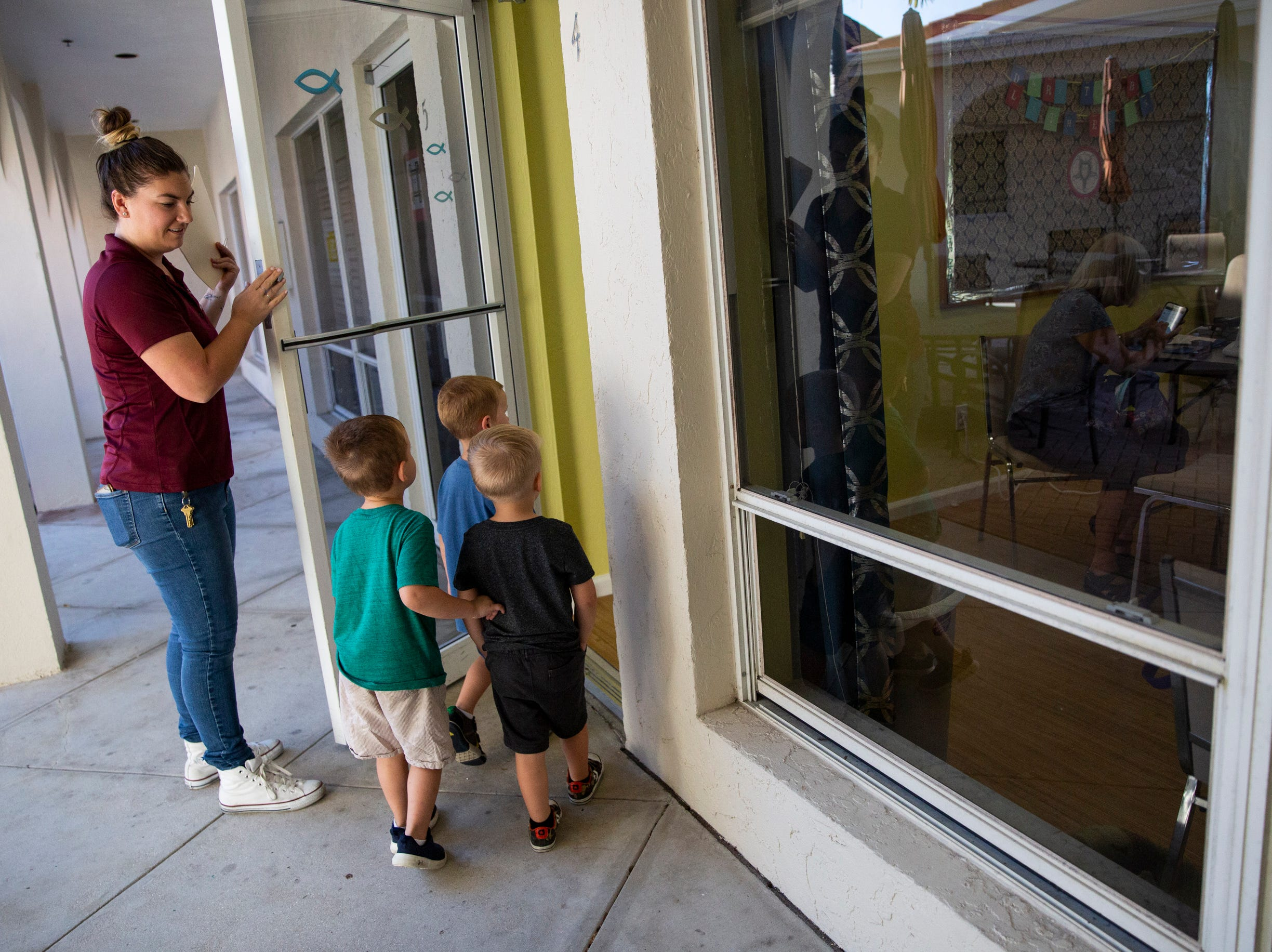 Preschool teacher Sissy Patton leads Carson Landis, 3, Logan Brann, 3, and Kingston Kellam, 4, into a room to have their hearing tested at Grace Lutheran Preschool in Naples on Friday, April 12, 2019.