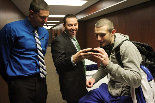 FGCU assistant coach Michael Fly, center, and guard Brett Comer, right, watch highlights of FGCU's victory over Georgetown at the Wells Fargo Center in Philadelphia in 2013