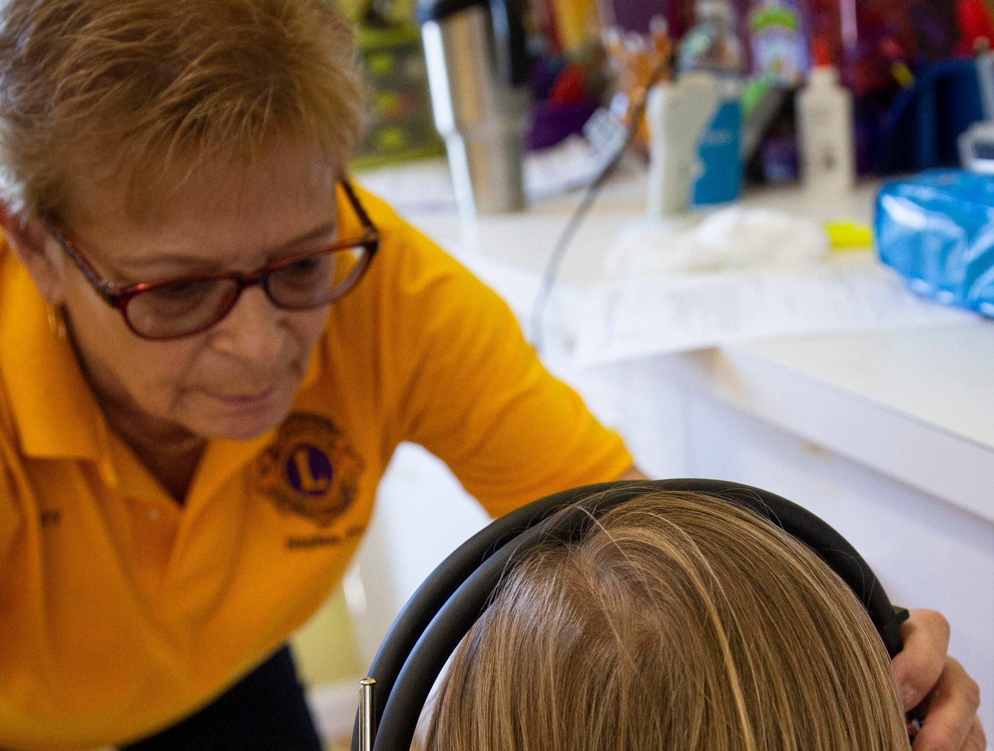 Volunteer Merry Hovey puts headphones on Colin Ryon, 4, so she can test his hearing at Grace Lutheran Preschool in Naples on Friday, April 12, 2019.