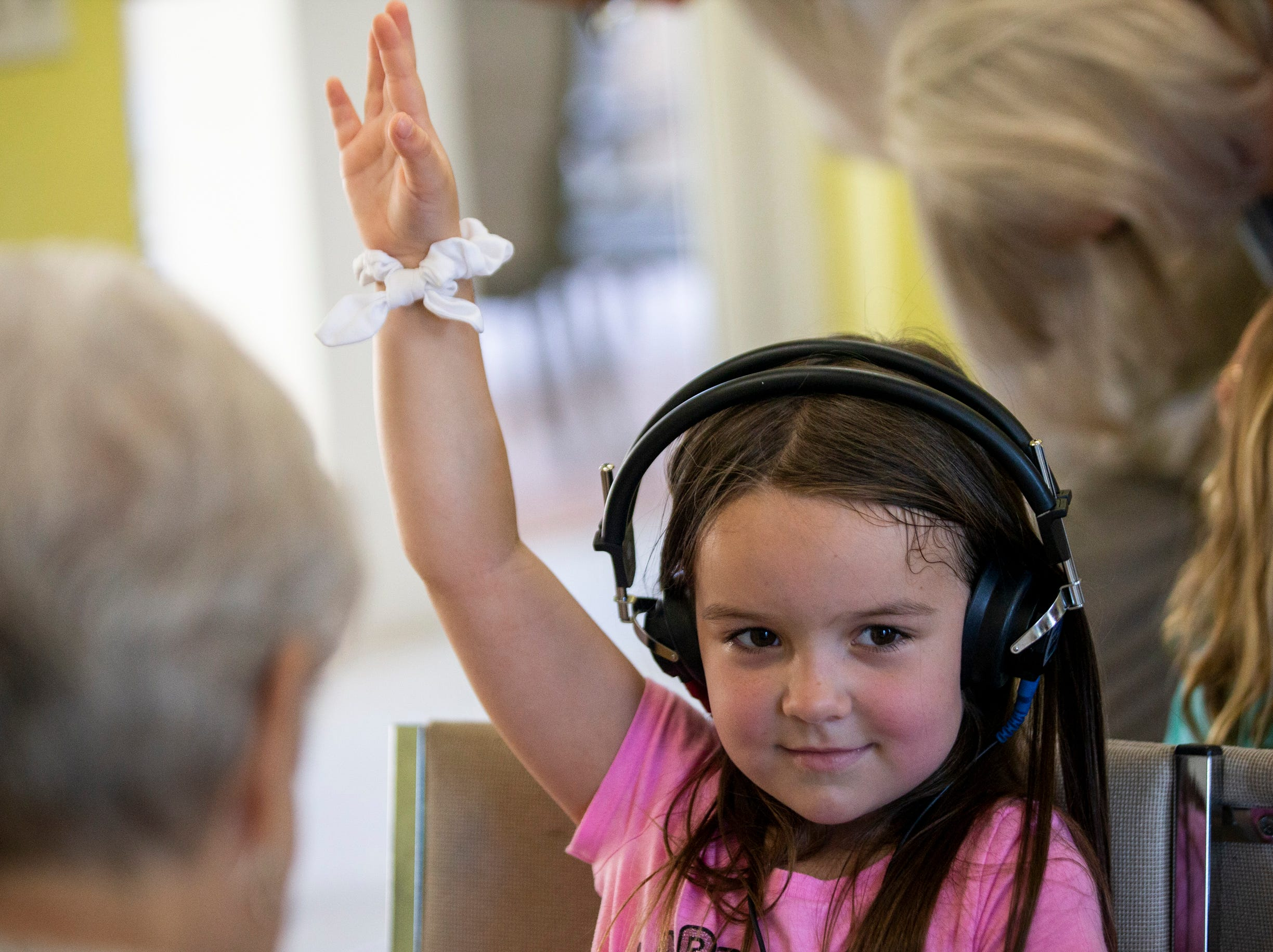 Stassi Seaman, 5, raises her hand to signal that she hears a noise coming through her headphones while she gets her hearing tested at Grace Lutheran Preschool in Naples on Friday, April 12, 2019.