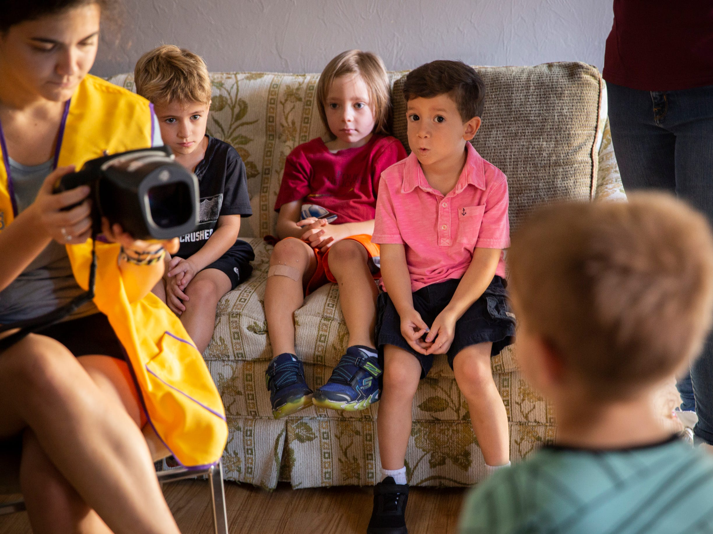 Michelle De Angelis tests Walker Barberio's eyes using a spot vision screener while, from left to right, Liam Willig, 5, Colin Ryan, 4, and Maxwell Florian, 5, watch at Grace Lutheran Preschool in Naples on Friday, April 12, 2019.