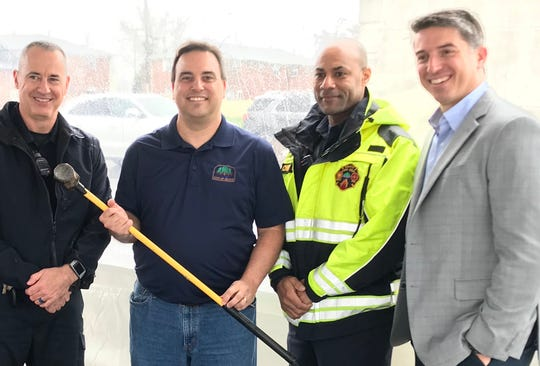 Heath Police Chief David Haren, Mayor Mark Johns, Fire Chief Warren McCord, and Eric Leibowitz, vice president of development for Casto, celebrate the upcoming demolition and redevelopment of the Knights Inn hotel site on Hebron Road.