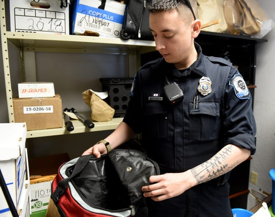Buckeye Lake Police patrolman Jeremy Jackson with a duffel bag found in evidence. Jackson has taken on helping clean, organize, and properly document evidence in the department's evidence lock up along with patrol duties. Police chief Vicki Wardlow and her officers have been working to inventory every item, but find most items provide minimal information as to what report they should be associated with. The Village is seeking a new five-year five-mills levy to fund the village's police department. The levy will be on the ballot this May and, if passed, the earliest Buckeye Lake can begin receiving funds from that is in 2020.