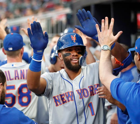 New York Mets' Amed Rosario (1) celebrities in the dugout after hitting a three-run home run during the second inning of the team's baseball game against the Atlanta Braves on Thursday, April 11, 2019, in Atlanta.