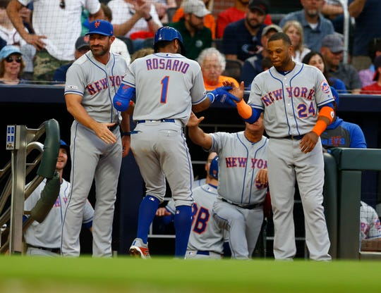 ATLANTA, GEORGIA - APRIL 11: Shortstop Ahmed Rosario #1 of the New York Mets is congratulated near the dugout after hitting a 3-run home run in the second inning during the game against the Atlanta Braves at SunTrust Park on April 11, 2019 in Atlanta, Georgia.